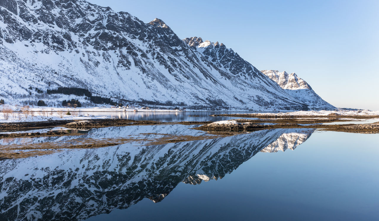 Panorama of mountain range reflecting in fjord Awe Beauty In Nature Blue Clear Sky Cold Temperature Fjord Getting Away From It All Idyllic Landscape Lofoten And Vesteral Islands Majestic Mountain Mountain Range Nature Nature Panoramic Polar Climate Reflection Remote Scenics Sky Snow Tranquility Water Winter