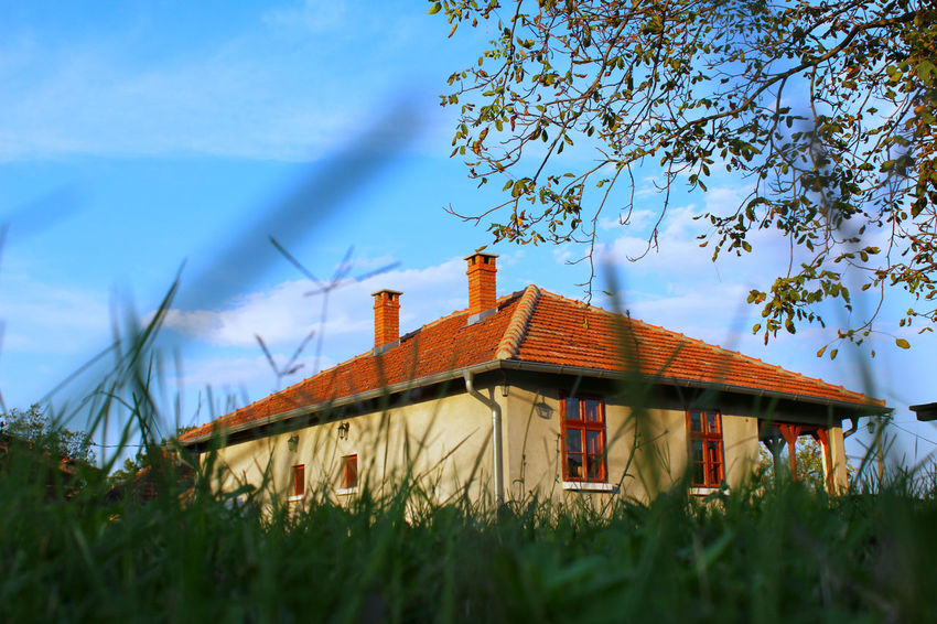 Old looking Serbian house in Gornji Adrovac village in Serbia. The place where Russian colonel Nikolay Raevsky died. Raevsky, who inspired Tolstoy to create the legendary count Vronsky, the lover of Anna Karenina, died defending Serbia from the Turks, near the village of Gornji Adrovac. Architecture Barn Beauty In Nature Blue Building Exterior Built Structure Cloud Cloud - Sky Day Field Grass Grassy Green Color Growth House Landscape Nature No People Outdoors Plant Residential Structure Rural Scene Sky Tranquil Scene Tranquility