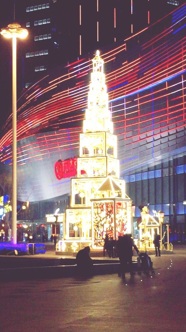 illuminated, night, building exterior, built structure, architecture, real people, christmas, celebration, street, city, men, city life, lifestyles, christmas decoration, women, christmas lights, outdoors, one person, carousel, sky, people
