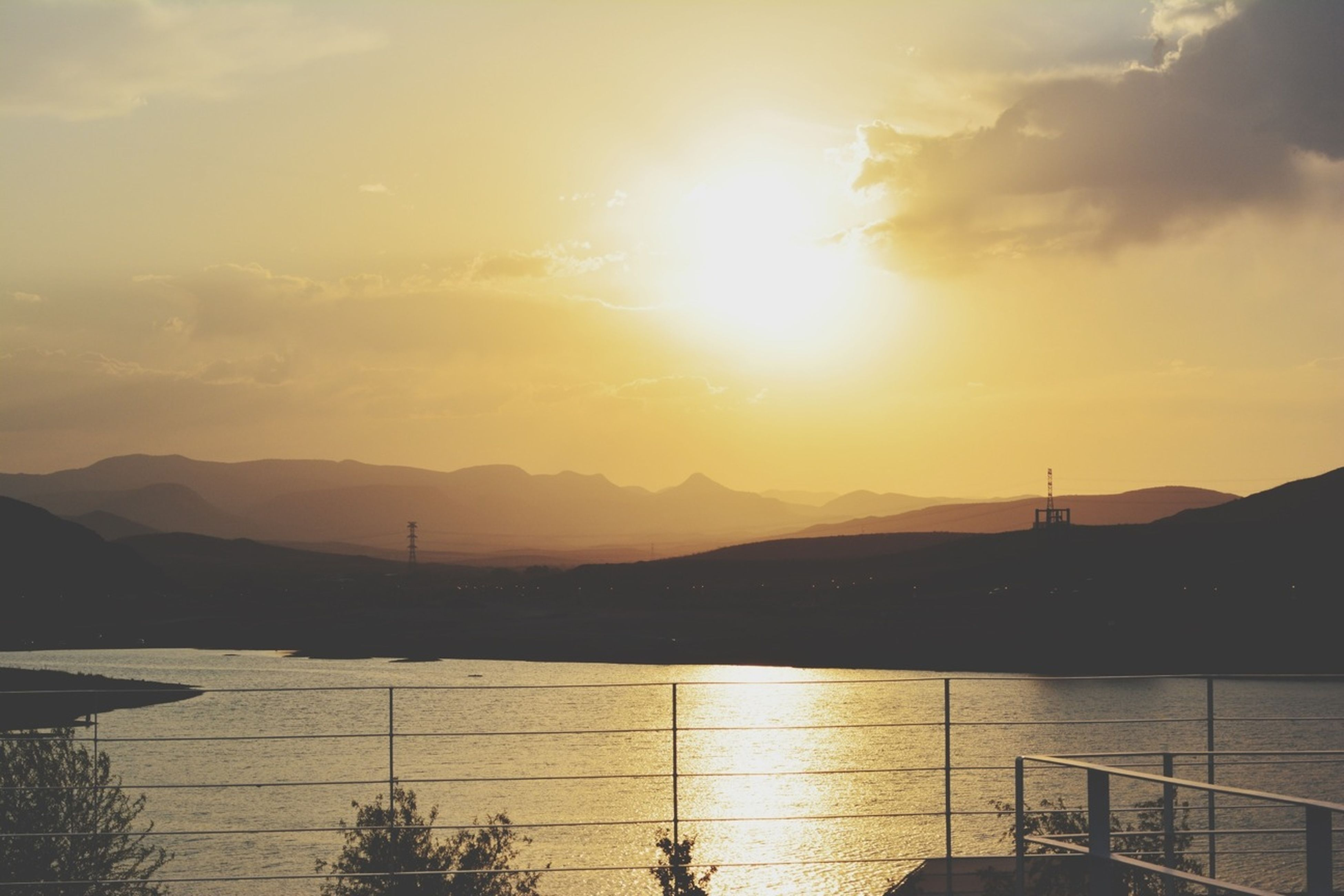 sunset, mountain, sun, water, mountain range, scenics, tranquil scene, silhouette, beauty in nature, tranquility, sky, lake, reflection, nature, sunlight, idyllic, cloud - sky, sunbeam, river, orange color
