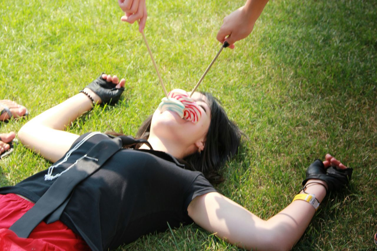 grass, childhood, leisure activity, girls, high angle view, outdoors, day, eyes closed, boys, casual clothing, two people, elementary age, real people, child, lying down, holding, lifestyles, animal themes, human hand, people