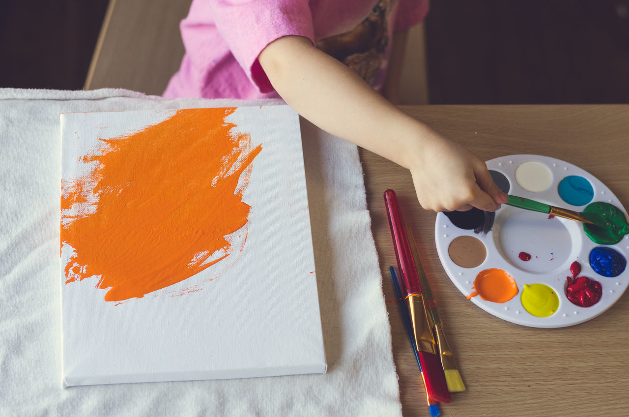 Child painting making art Activity Art Canvas Child Childhood Children Only Creating Creativity Drawing - Activity Girls High Angle View Holding Human Hand Indoors  Kids Being Kids Lifestyles One Girl Only One Person Orange Color Paint Paint Brush Painting Painting Art Real People Table