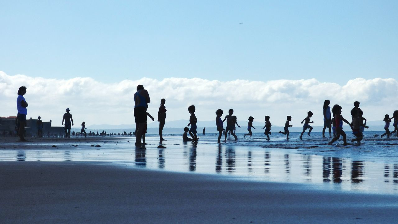 Beach Water Silhouette Sky Large Group Of People People Outdoors Day Wave Sea Children Playing On Beach Excitement Togetherness Leisure Activity Sunlight Wave Sand Beach Life Walking Vacation Time Silhouette