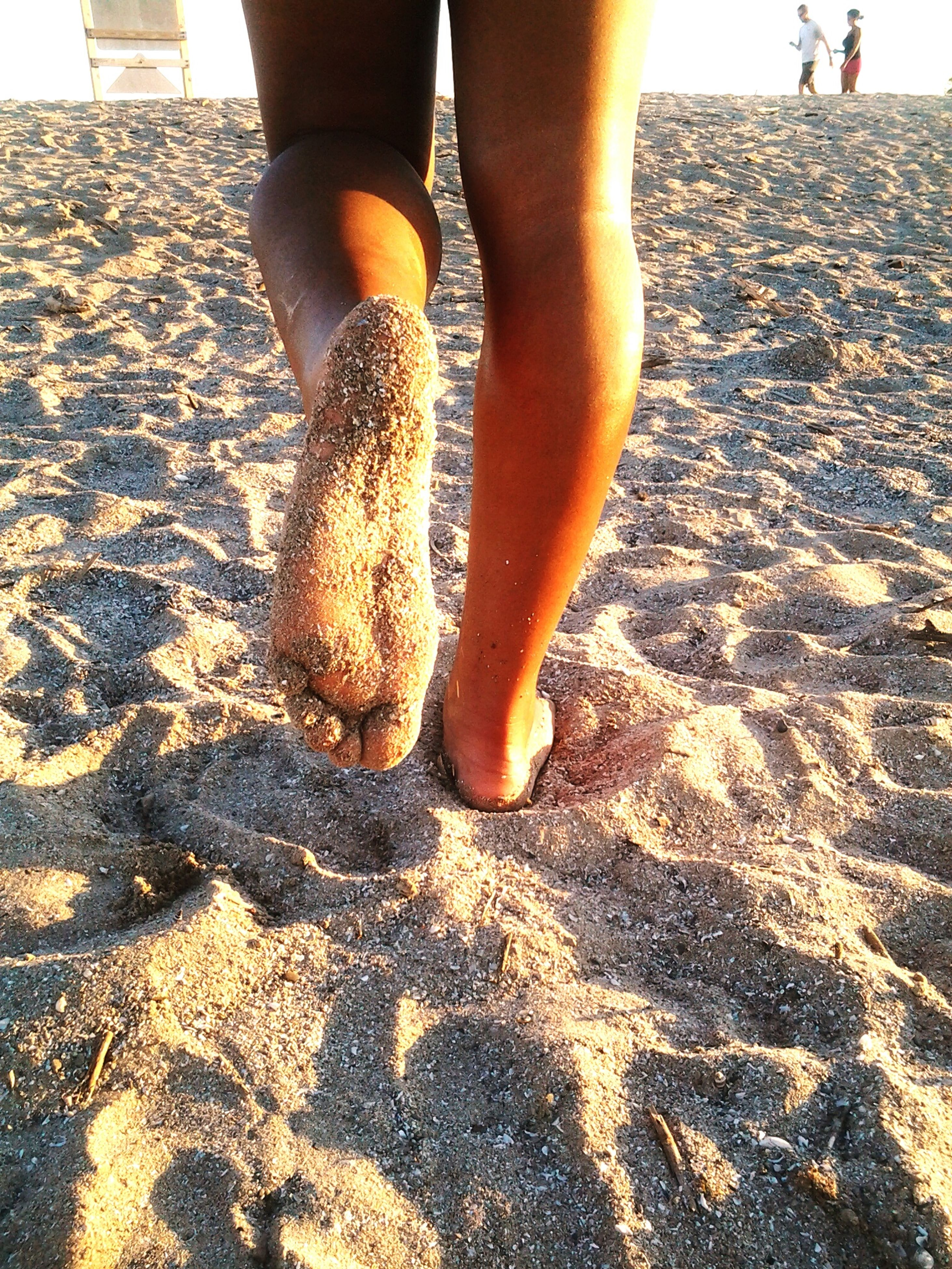 low section, person, beach, lifestyles, leisure activity, sunlight, human foot, barefoot, shore, outdoors, unrecognizable person, day, vacations, part of, nature, sunny
