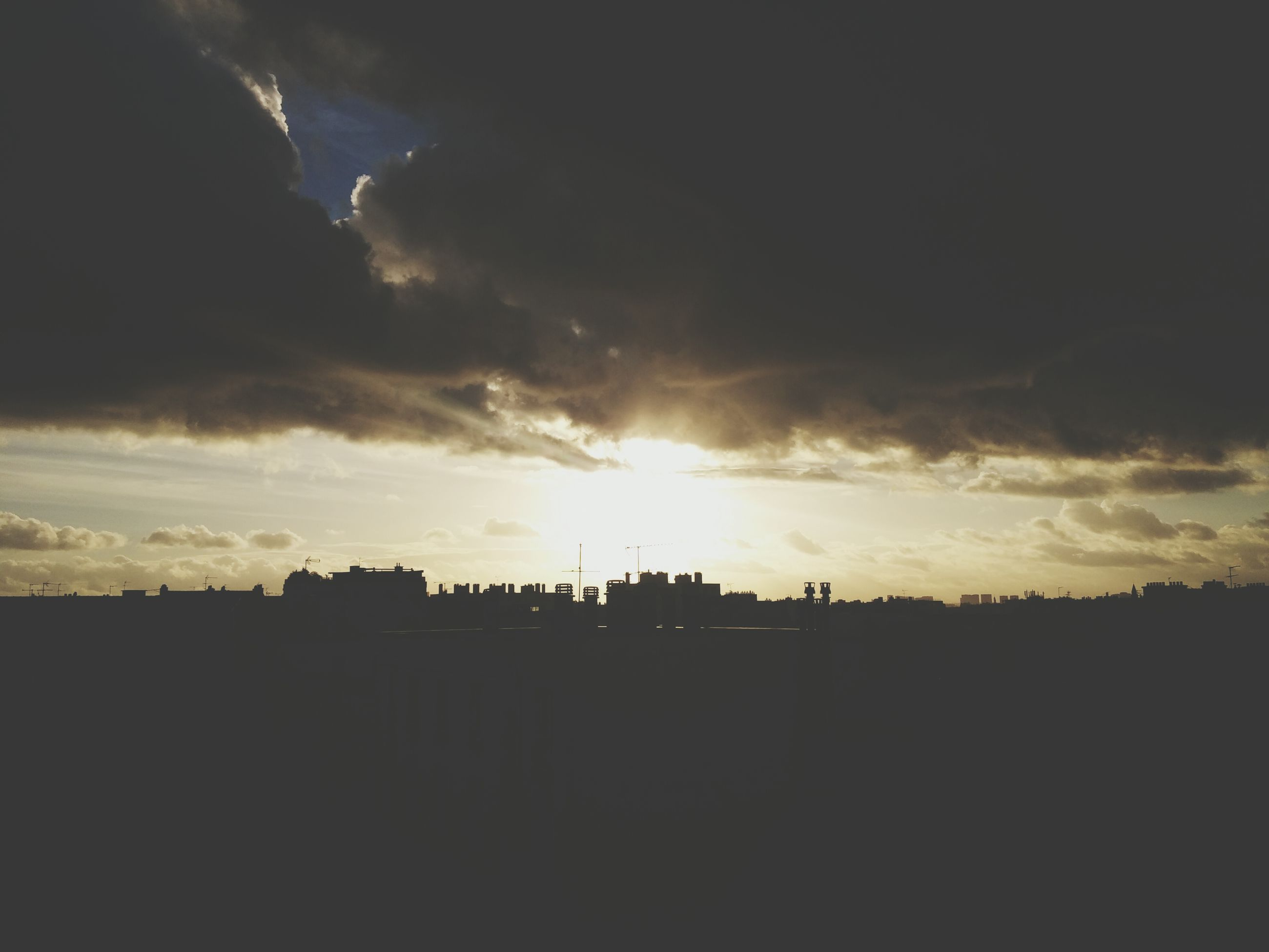 sunset, silhouette, sky, sun, cloud - sky, sunlight, built structure, sunbeam, scenics, beauty in nature, cloud, nature, building exterior, architecture, cloudy, tranquility, tranquil scene, low angle view, outdoors, landscape