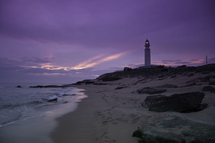 Purple skies Architecture Beach Beauty In Nature Building Exterior Built Structure Calm Coastline Direction Dusk Guidance Lighthouse Nature Non-urban Scene Outdoors Protection Safety Scenics Sea Shore Sky Sunset Tower Tranquil Scene Tranquility Water