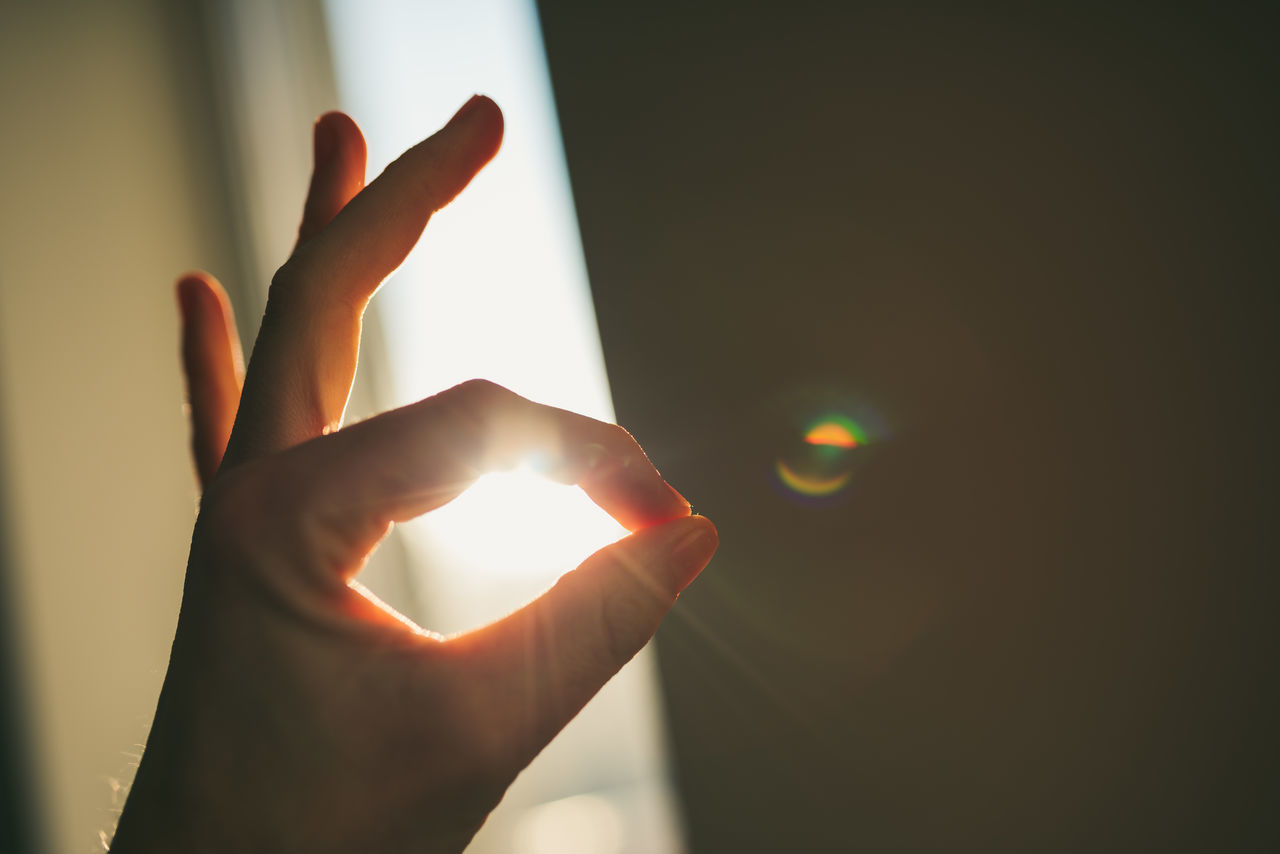 Close-Up Of Hand Gesturing Against Window