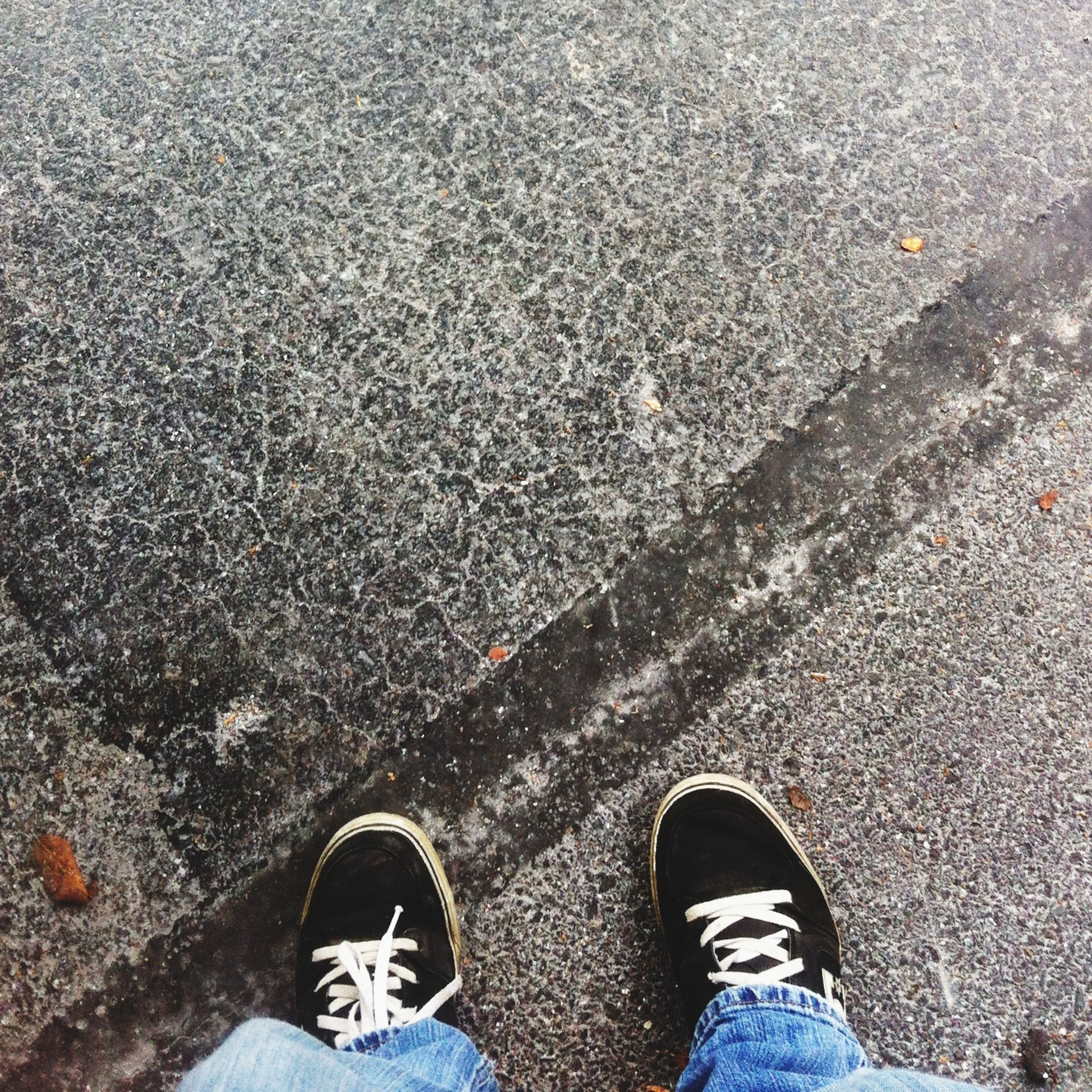 low section, person, shoe, personal perspective, standing, human foot, footwear, high angle view, street, jeans, lifestyles, men, unrecognizable person, asphalt, leisure activity, directly above, road