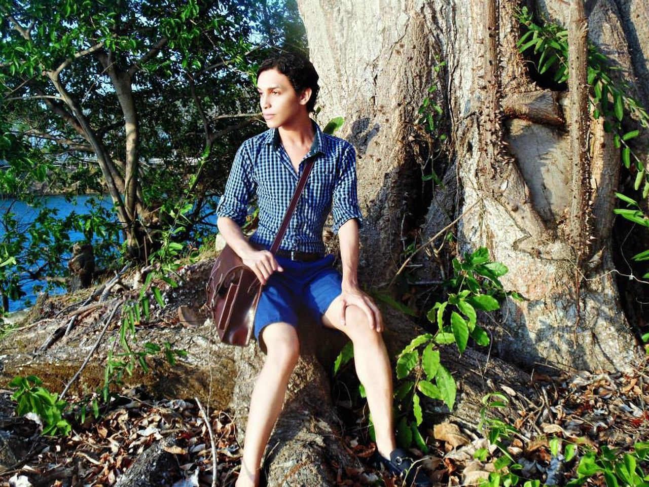 tree, casual clothing, one person, outdoors, forest, sitting, young adult, nature, front view, plant, day, smiling, tree trunk, happiness, full length, real people, young women, growth, only women, people, adults only, beauty in nature, adult, one woman only, one young woman only
