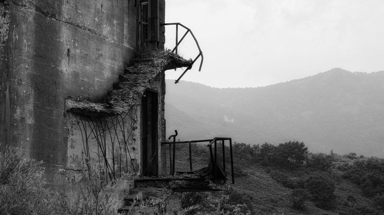 Broken stairway on exterior of ruined building in ghost town. Architecture Built Structure Day Foggy Ghost Town Hill Japan Landscape Matsuo Kouzan Mountain Mountain Range No People Non Urban Scene Non-urban Scene Outdoors Remote Ruined Building Tranquil Scene