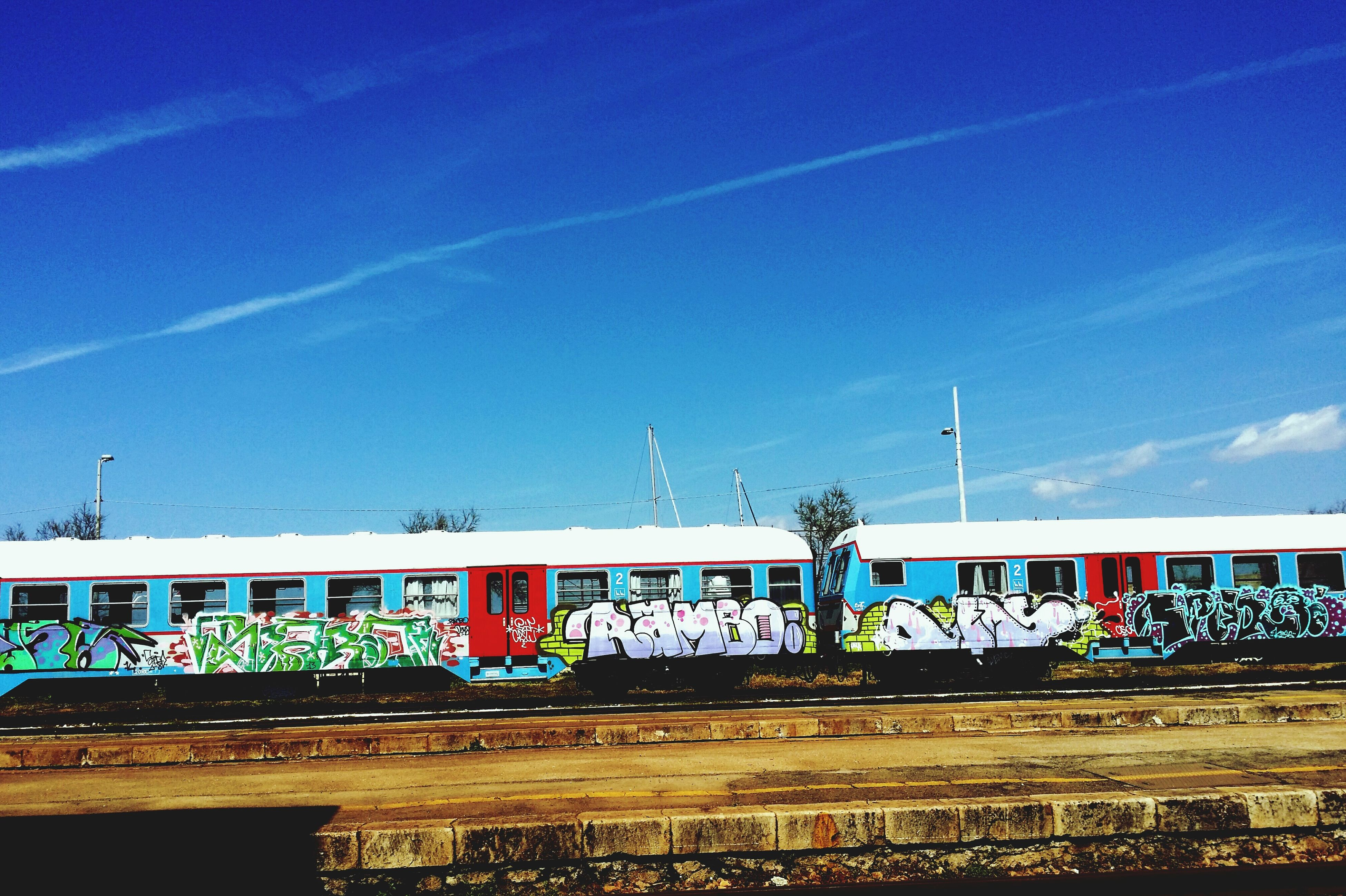 blue, sky, built structure, architecture, text, transportation, building exterior, graffiti, western script, railing, outdoors, day, communication, no people, cloud - sky, multi colored, cloud, low angle view, art, tree
