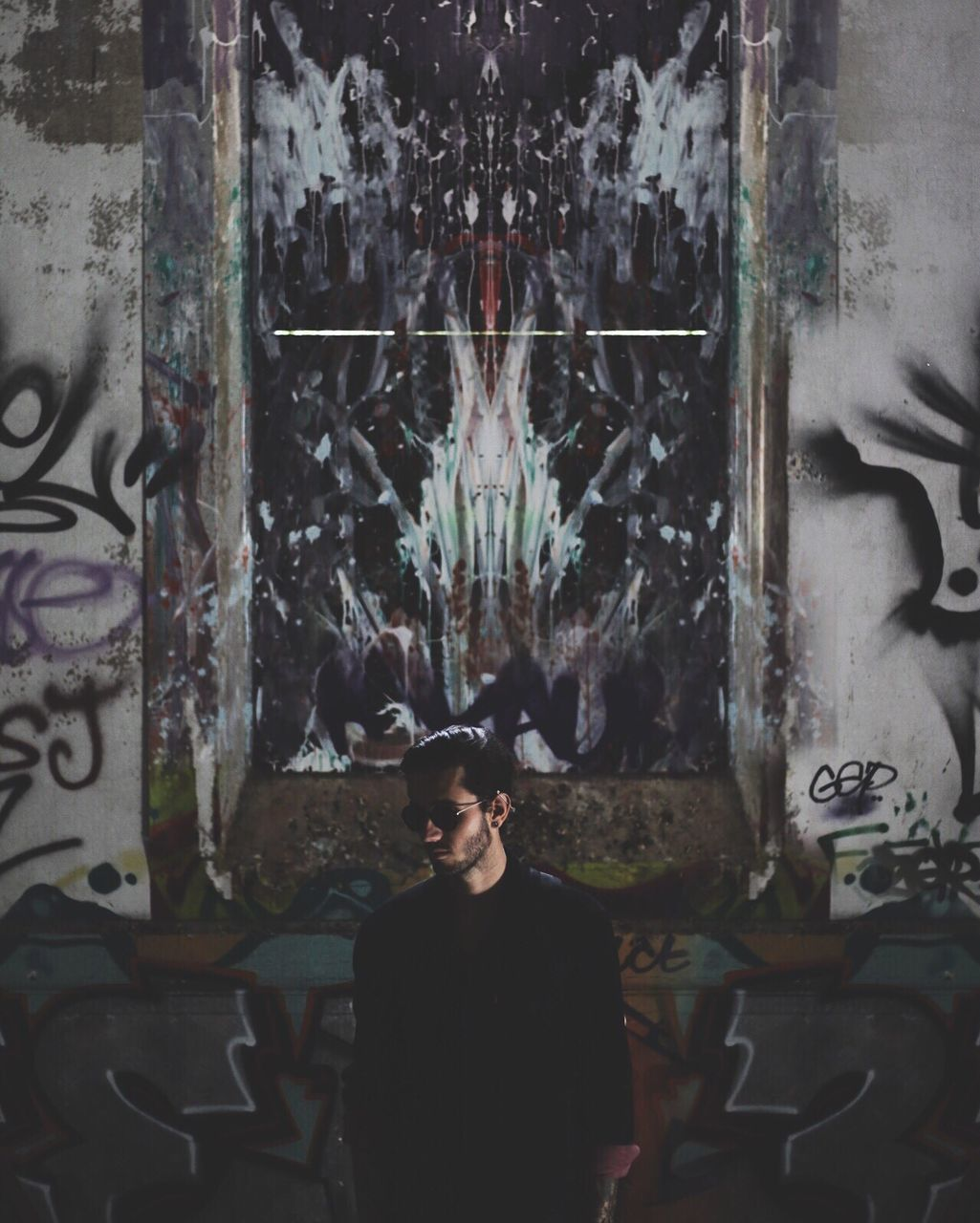 Young Man Standing Against Graffiti On Wall