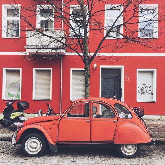 Red car in Berlin Red Architecture Building Exterior Built Structure Transportation Land Vehicle Mode Of Transport Car Stationary Outdoors Day No People Tree City Berlin Let's Go. Together. Neon Life Your Ticket To Europe Berlin Love