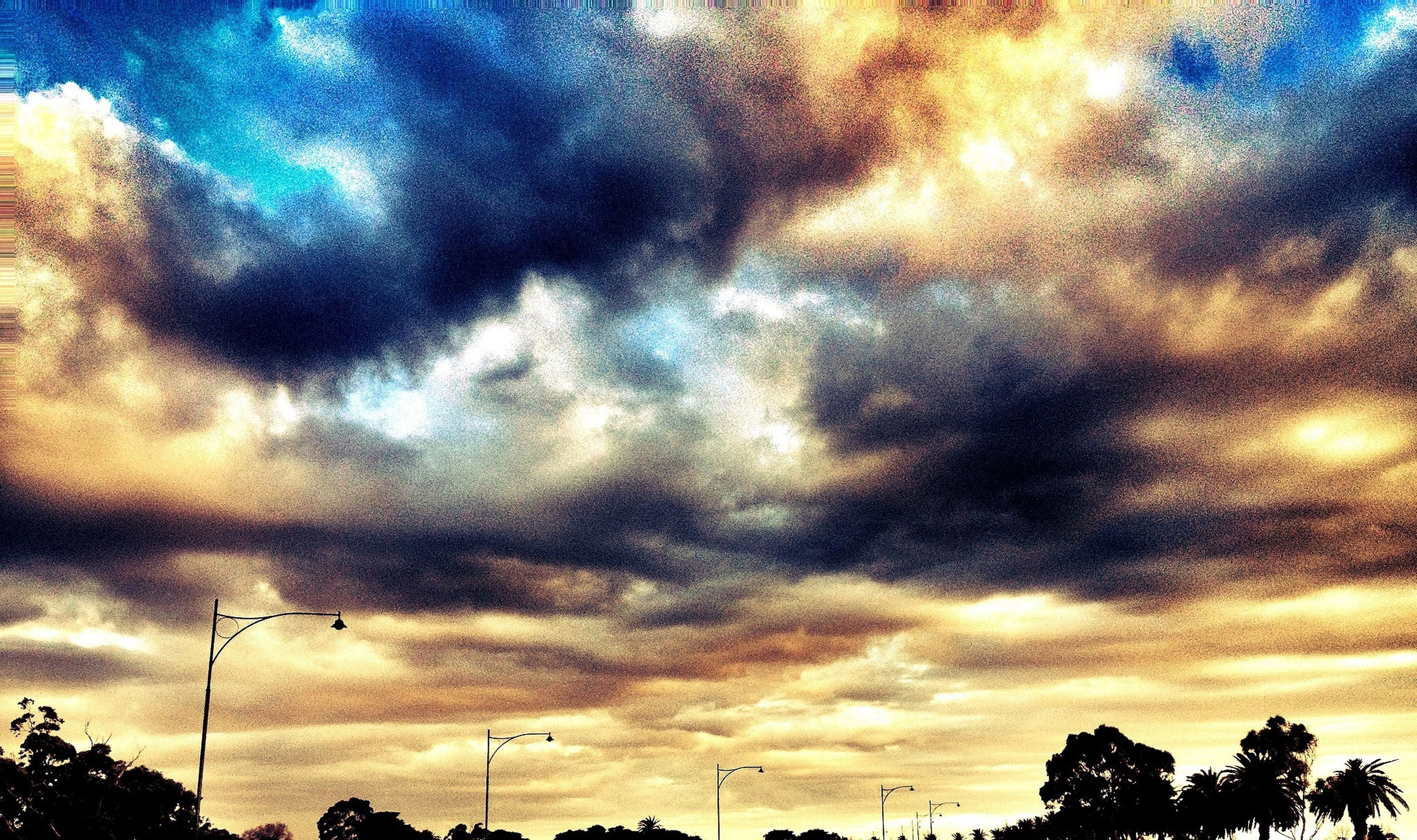 sky, cloud - sky, low angle view, silhouette, cloudy, tree, sunset, beauty in nature, scenics, dramatic sky, tranquility, weather, tranquil scene, nature, dusk, cloud, overcast, power line, street light, electricity pylon