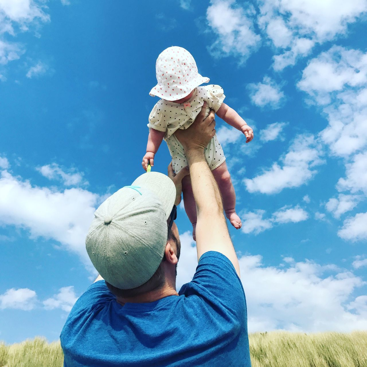 father, family with one child, childhood, sky, family, son, day, boys, field, low angle view, blue, real people, cloud - sky, leisure activity, casual clothing, outdoors, togetherness, daughter, nature, lifestyles, growth, playing, standing, men, bonding, tree, grass