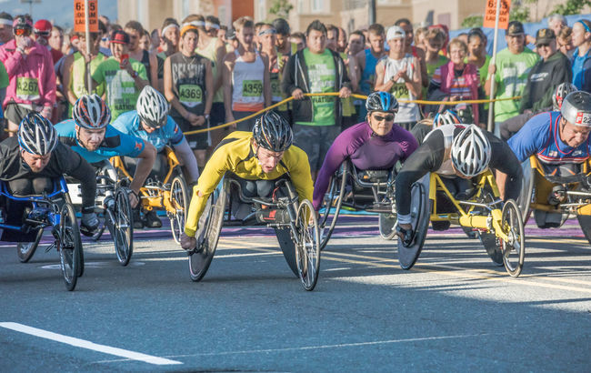 Elite wheelchair racers sprint at the start of a big road race. Athletes Competition Effort In A Row Men Multi Colored Need For Speed Outdoors Race Road Race Sprint Starting Line Wheelchair