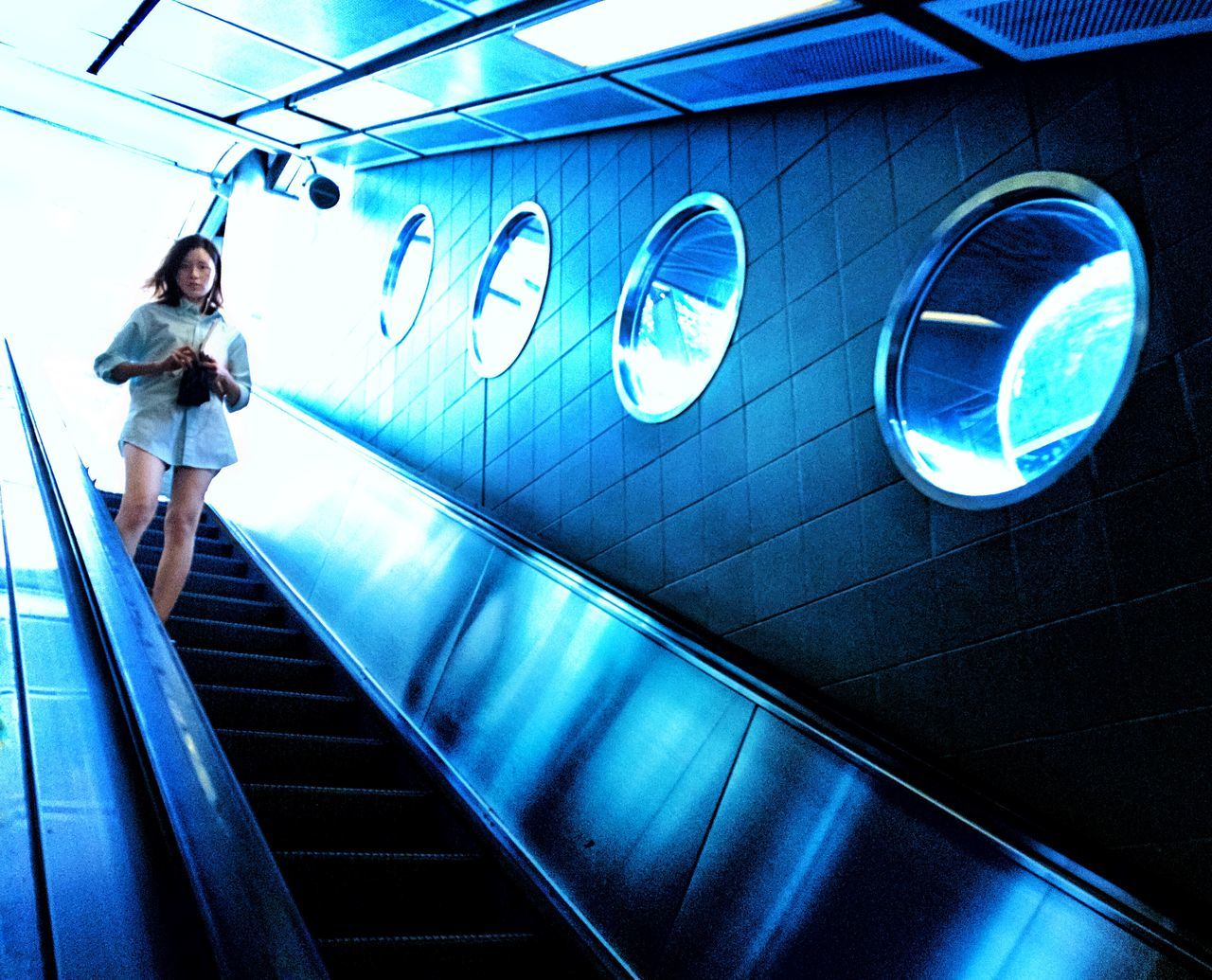 full length, real people, one person, lifestyles, illuminated, young adult, steps and staircases, casual clothing, leisure activity, low angle view, technology, indoors, young women, women, modern, architecture, day, adult, people