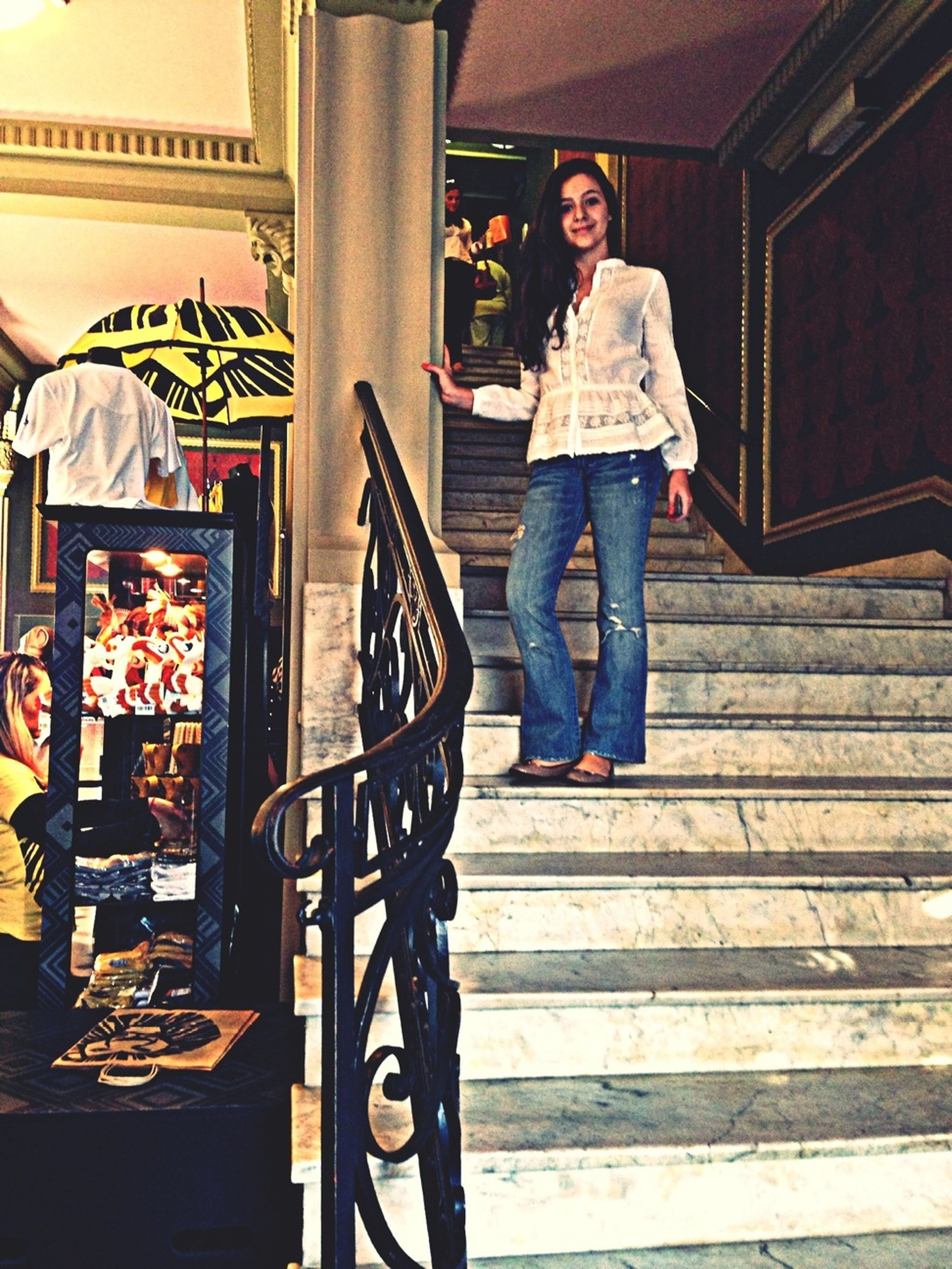 full length, lifestyles, casual clothing, young adult, steps, person, architecture, built structure, front view, young women, leisure activity, indoors, standing, steps and staircases, staircase, looking at camera, portrait, building exterior