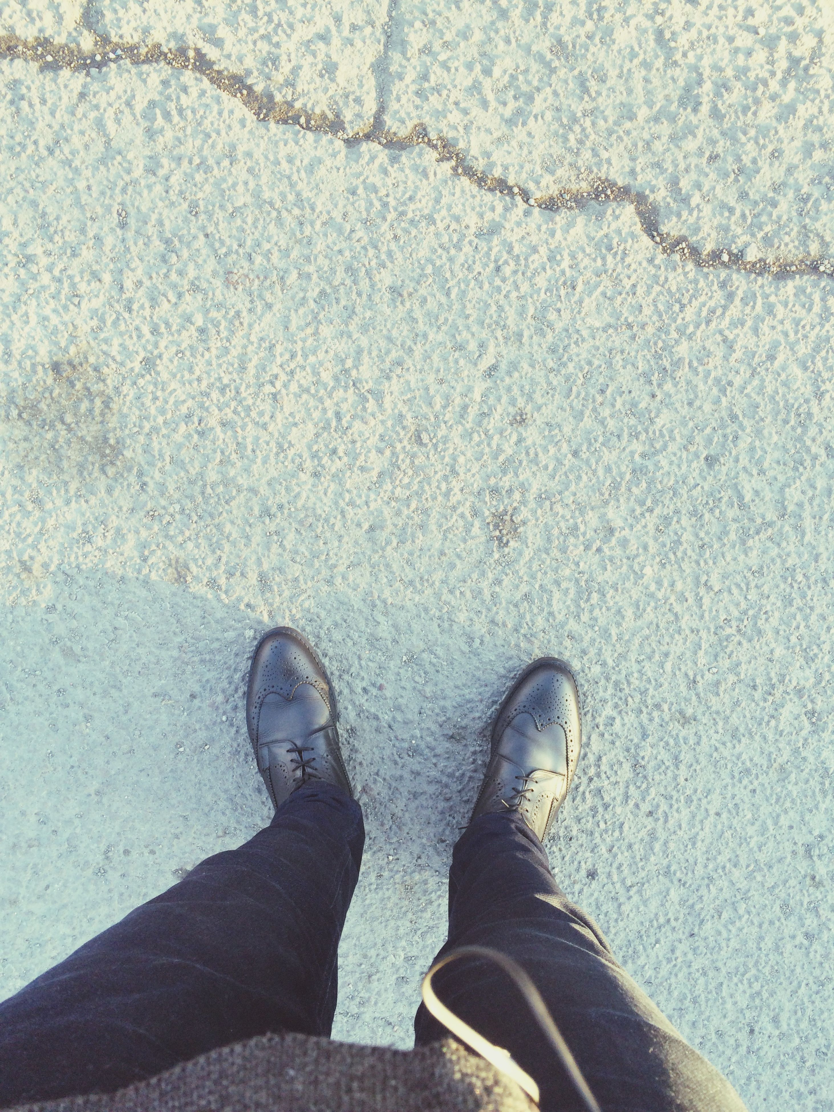 low section, person, personal perspective, shoe, standing, high angle view, lifestyles, human foot, footwear, street, men, leisure activity, shadow, directly above, jeans, unrecognizable person, road