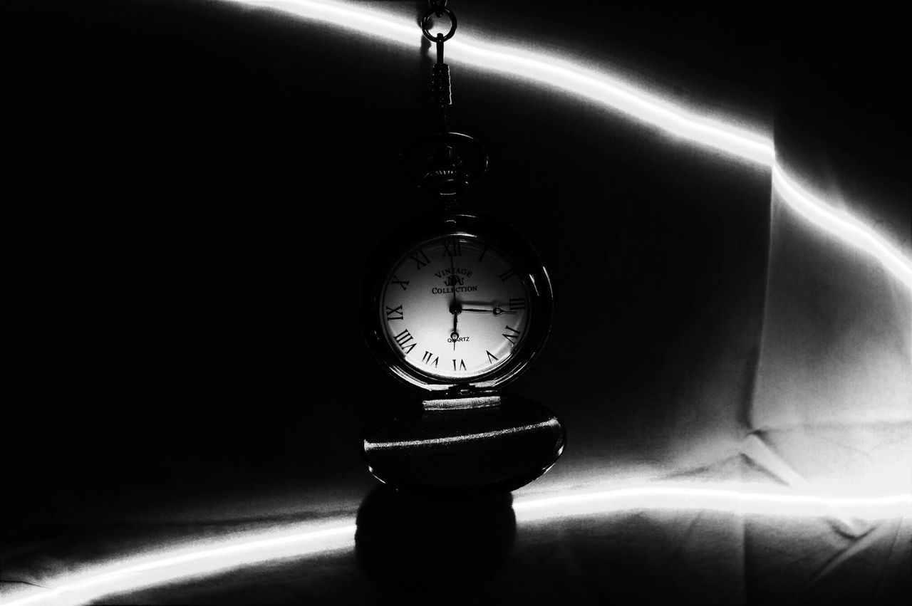 A pocket watch dangling from above is illuminated by a trail of light Time Clock Indoors  Close-up Blackandwhite Shadow