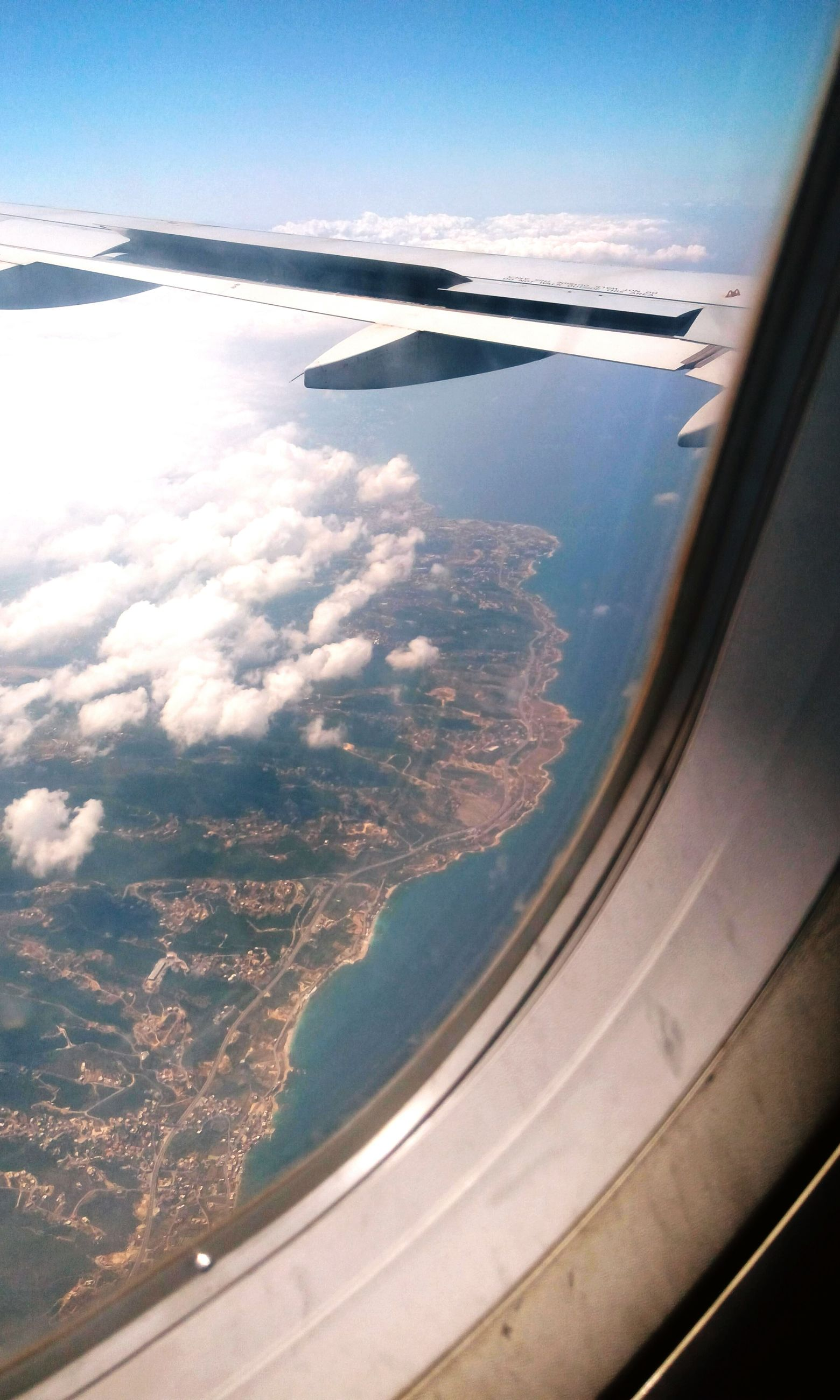aerial view, airplane, transportation, airplane wing, beauty in nature, nature, scenics, journey, window, vehicle part, landscape, no people, aircraft wing, air vehicle, mode of transport, travel, flying, day, sky, mountain, mid-air, sea, outdoors, view into land, water