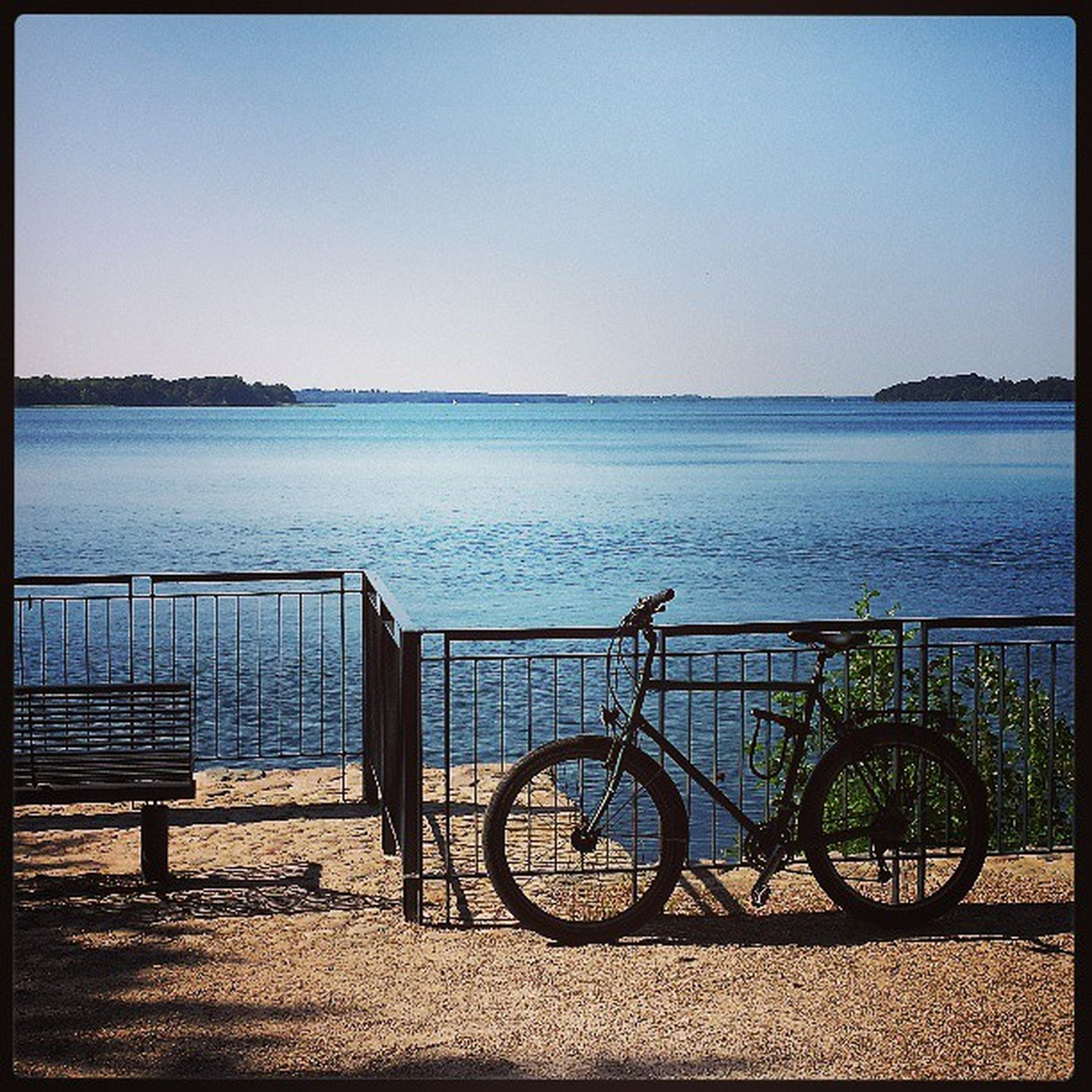 water, sea, clear sky, horizon over water, copy space, bicycle, beach, tranquility, transfer print, tranquil scene, railing, shore, scenics, nature, sky, auto post production filter, beauty in nature, blue, transportation, mode of transport