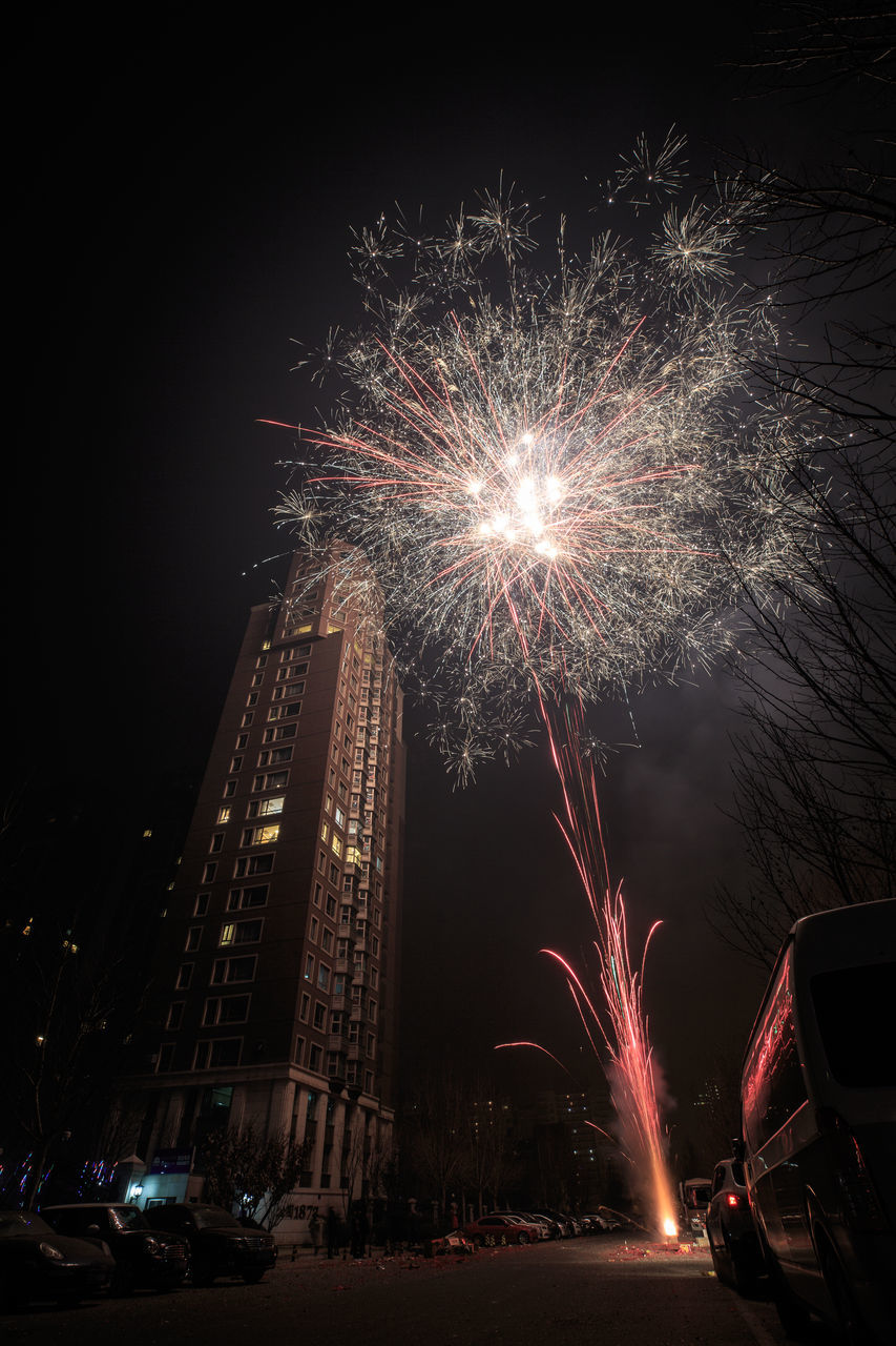 night, firework display, exploding, illuminated, celebration, firework - man made object, motion, sparks, long exposure, glowing, blurred motion, firework, event, arts culture and entertainment, low angle view, car, outdoors, sky, built structure, building exterior, architecture, no people, city, multi colored