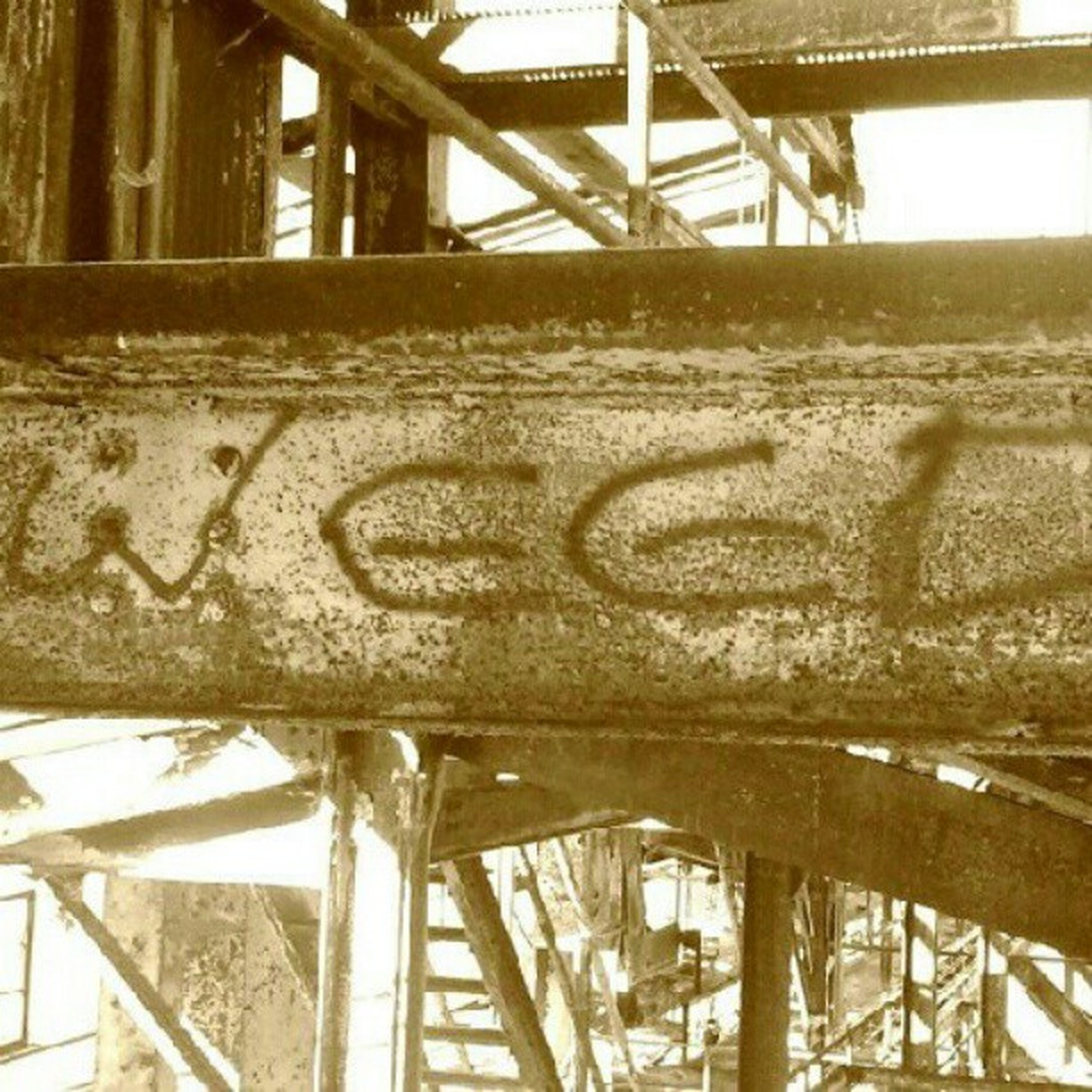built structure, metal, architecture, metallic, railing, text, rusty, wood - material, day, western script, connection, no people, wooden, bridge - man made structure, graffiti, outdoors, pattern, close-up, sky, low angle view