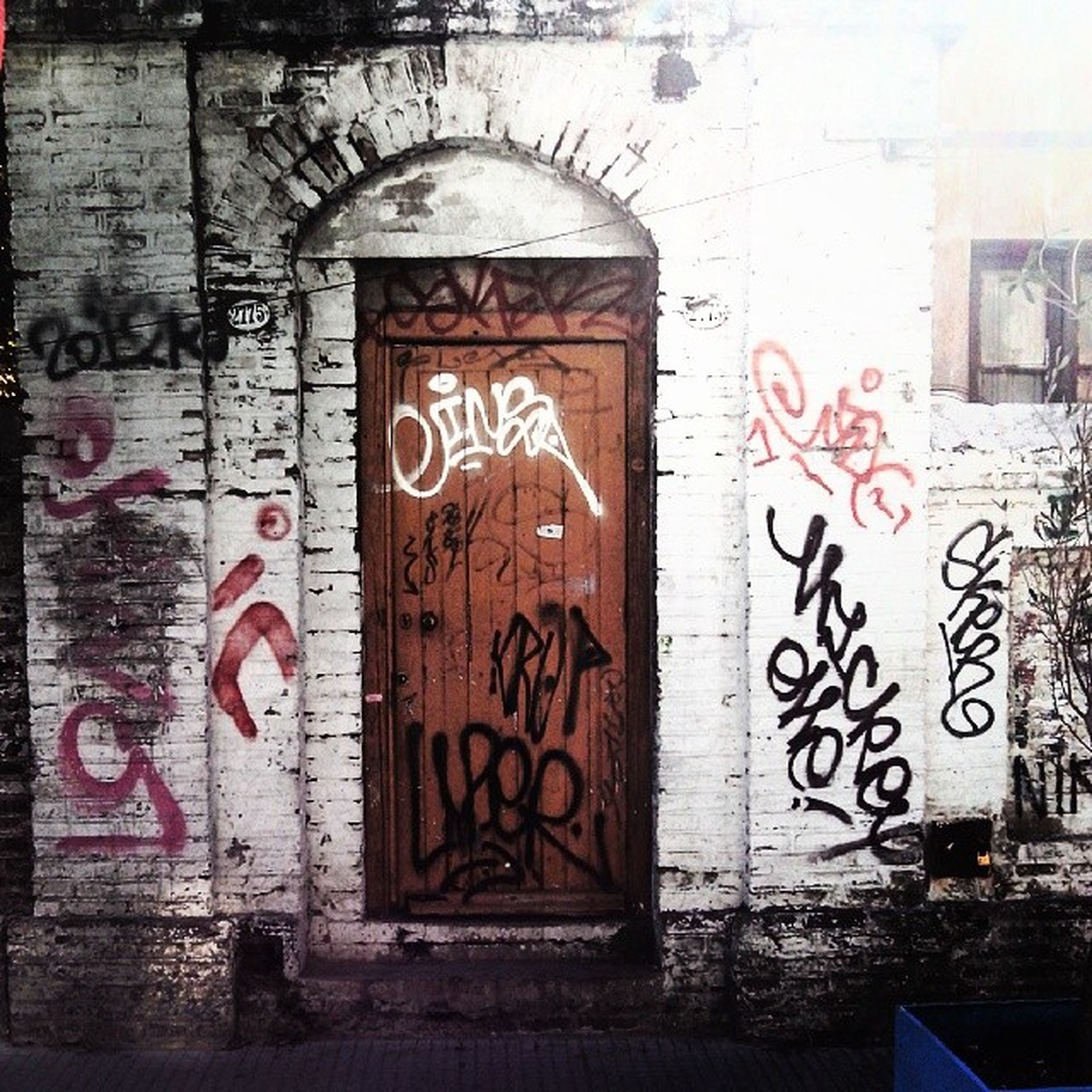graffiti, architecture, built structure, wall - building feature, text, building exterior, western script, wall, communication, brick wall, weathered, door, art, creativity, old, abandoned, damaged, art and craft, vandalism, street art