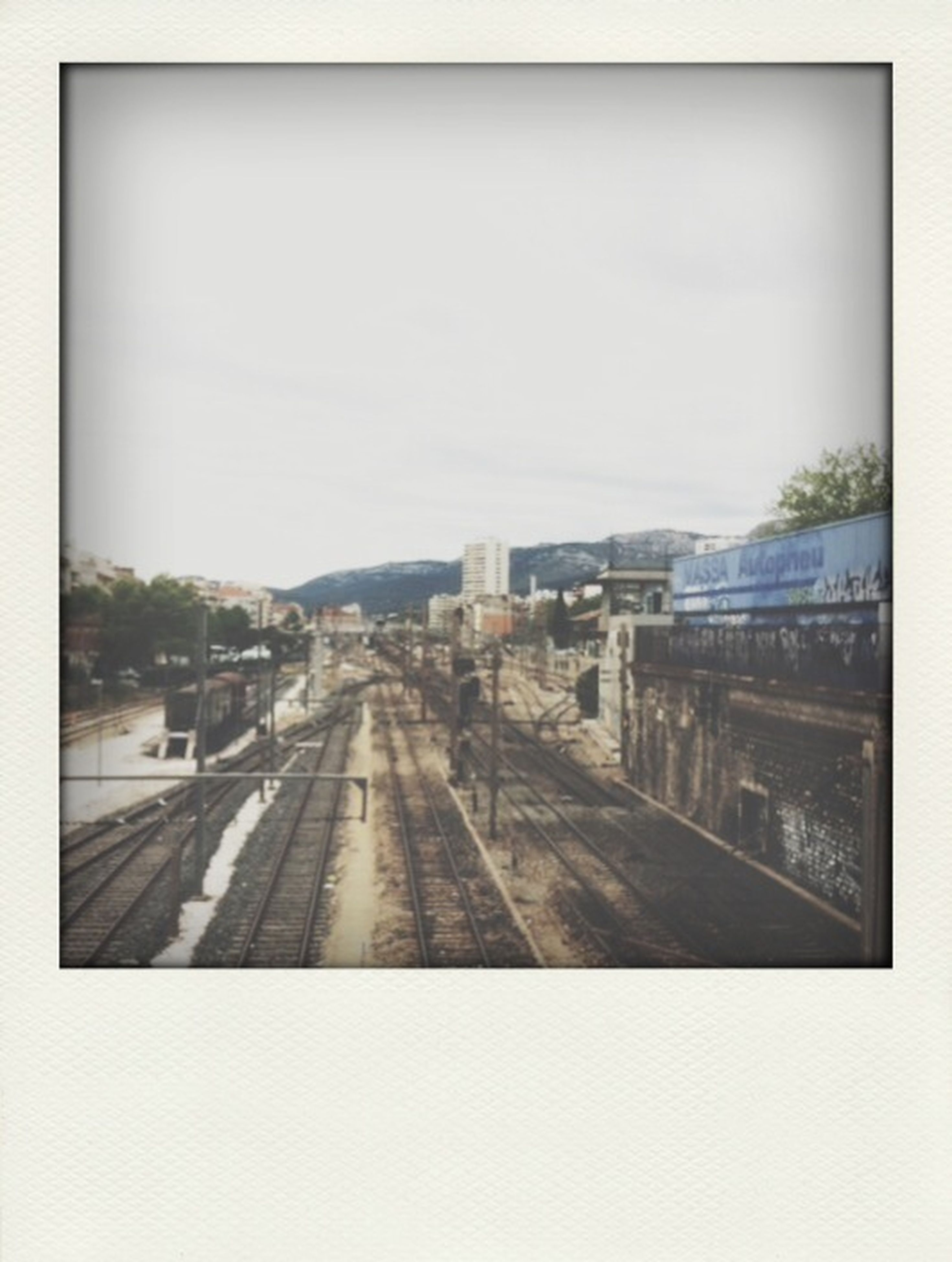 transportation, transfer print, auto post production filter, mode of transport, car, road, architecture, land vehicle, sky, built structure, building exterior, the way forward, city, clear sky, diminishing perspective, railroad track, glass - material, road marking, public transportation, vanishing point