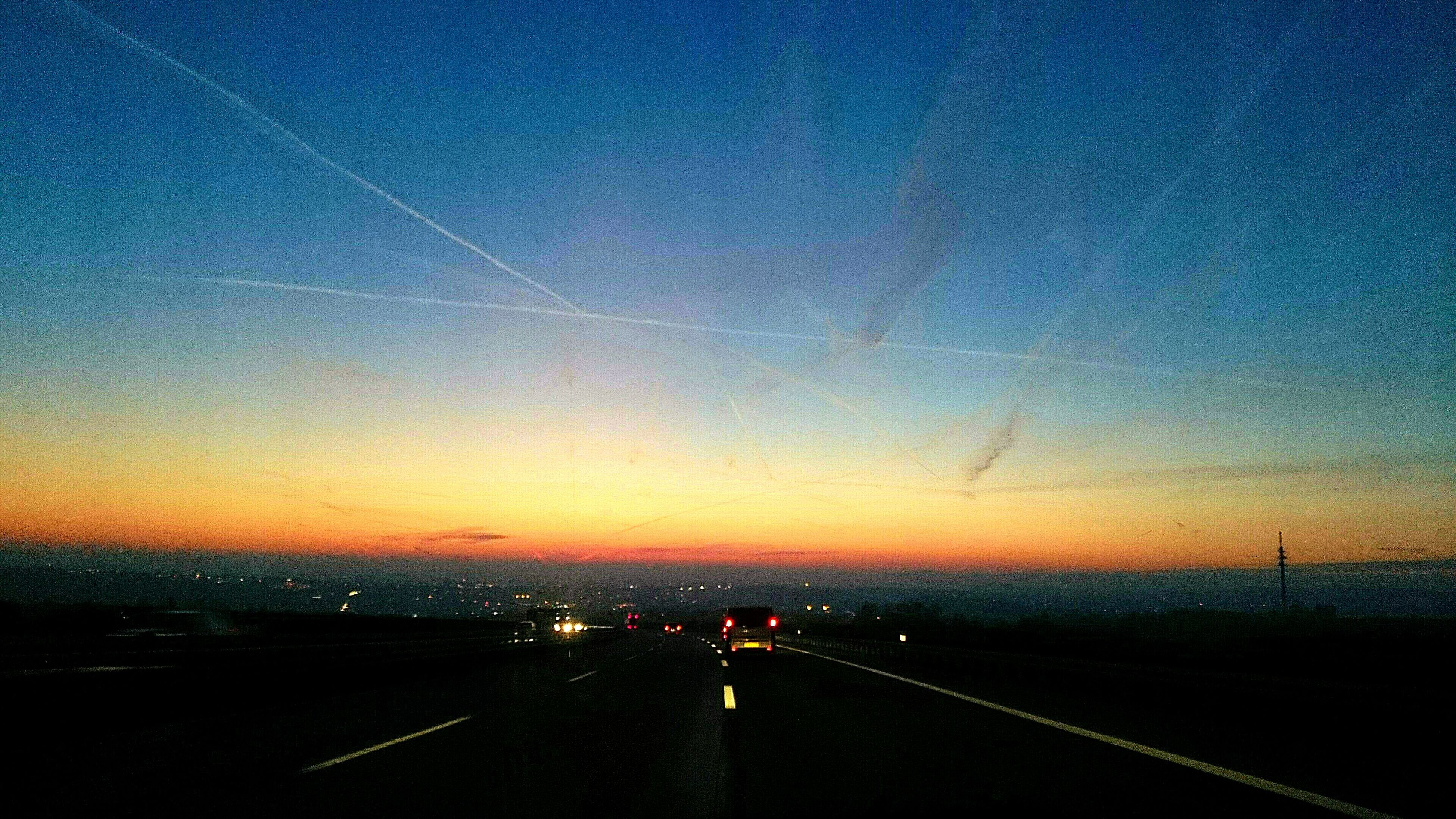 sunset, road, transportation, sky, landscape, blue, illuminated, dusk, city, scenics, copy space, the way forward, high angle view, street, tranquil scene, road marking, tranquility, nature, no people, outdoors