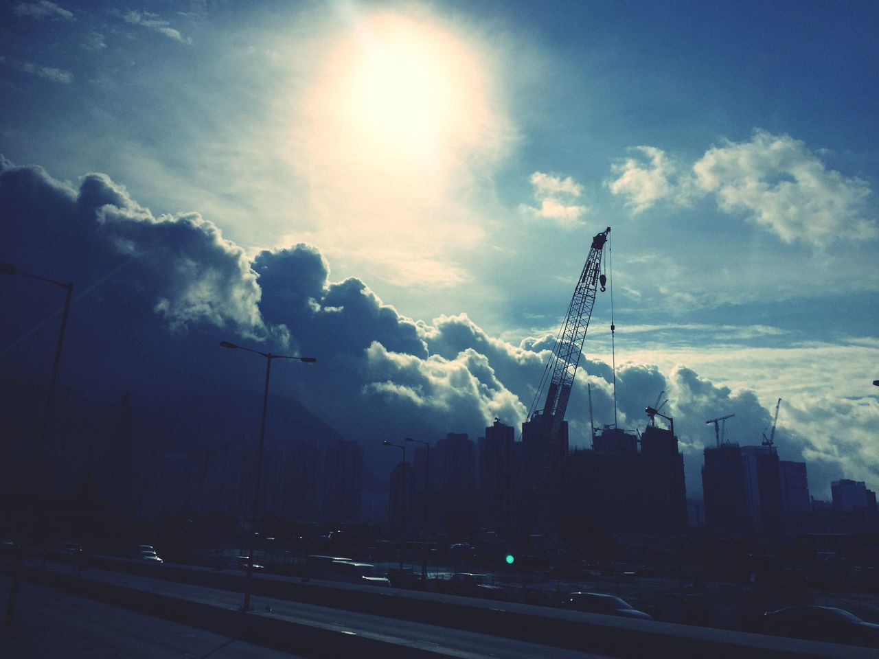 sky, cloud - sky, lens flare, outdoors, architecture, built structure, sunlight, building exterior, smoke stack, no people, factory, industry, road, day, city, nature