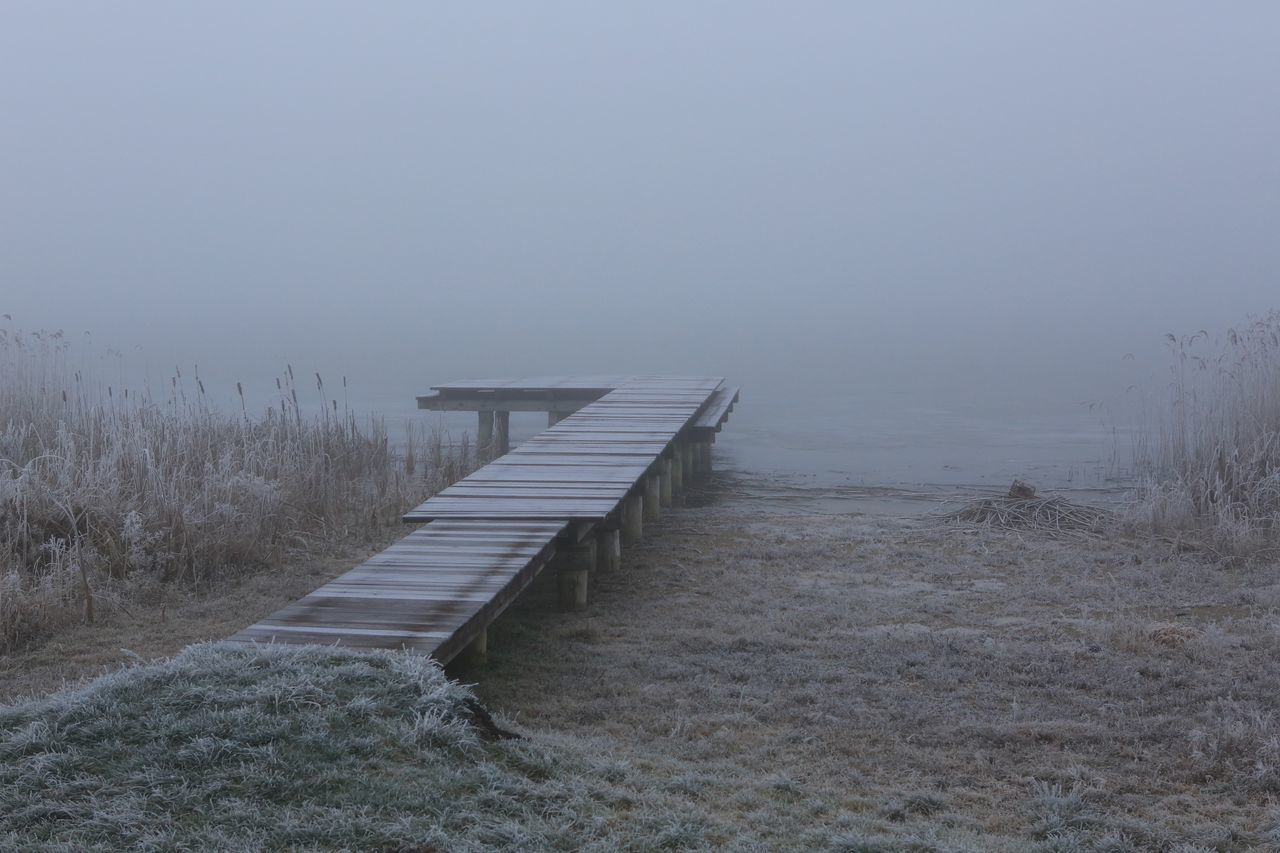 Pier At Lakeshore Against Sky During Foggy Weather