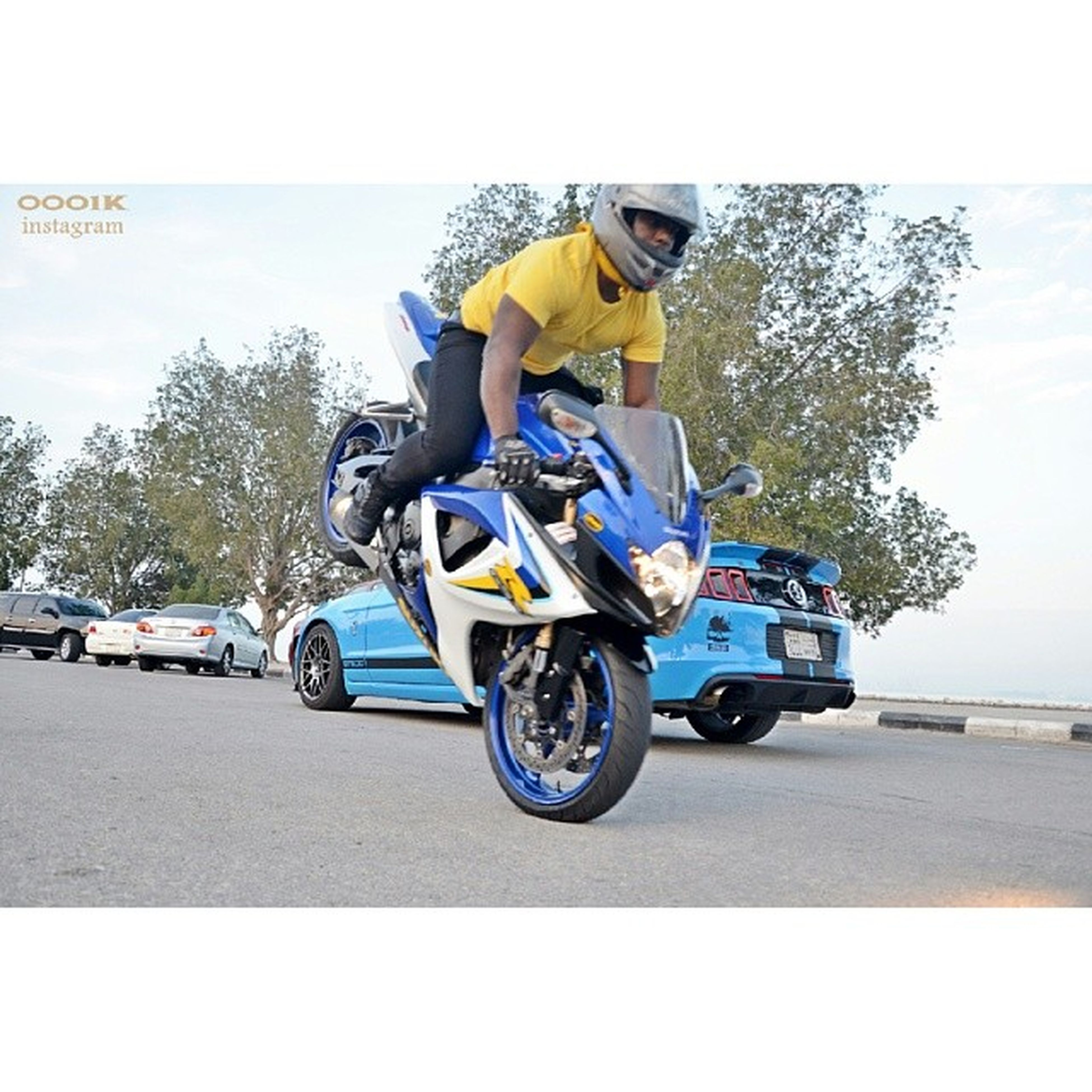 transportation, mode of transport, land vehicle, bicycle, car, stationary, clear sky, tree, parked, parking, travel, sunlight, street, road, day, yellow, motorcycle, riding, side view, on the move