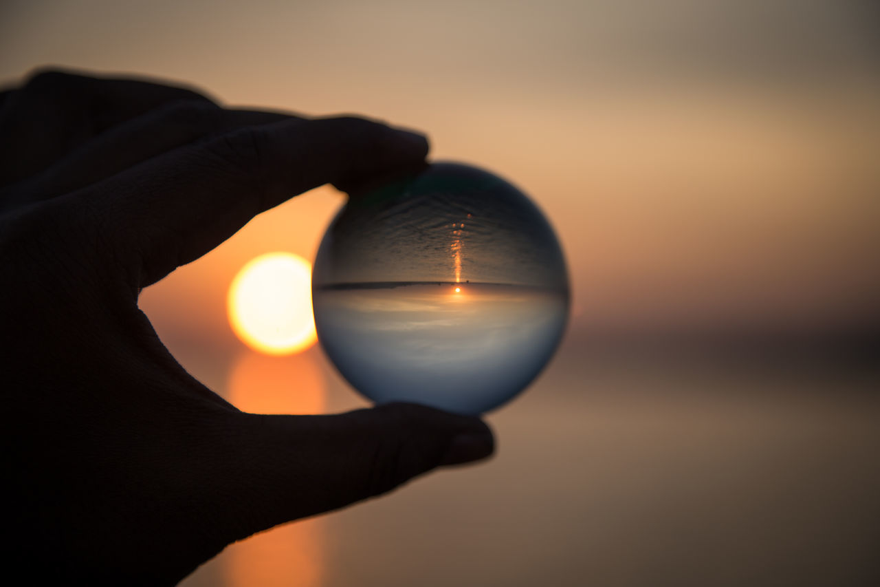 Through my Crystel Ball Circle Close-up Crystal Ball Fortune Telling Holding Human Body Part Human Hand Illuminated One Person Outdoors People Reflection River Sky Sphere Sun Sunrise