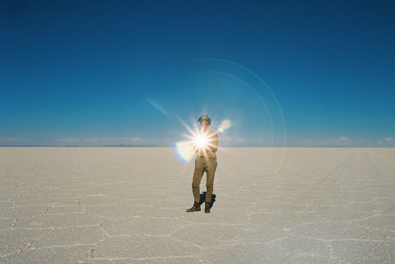 Filmisnotdead Sunlight Sun Lens Flare Clear Sky Full Length Real People Blue Sky Outdoors Sunbeam Nature One Person Standing Sand Men Beauty In Nature Day Motion Human Hand Wire Wool Uyuni Salt Flat Bolivia People Film Is Not Dead The Week On EyeEm
