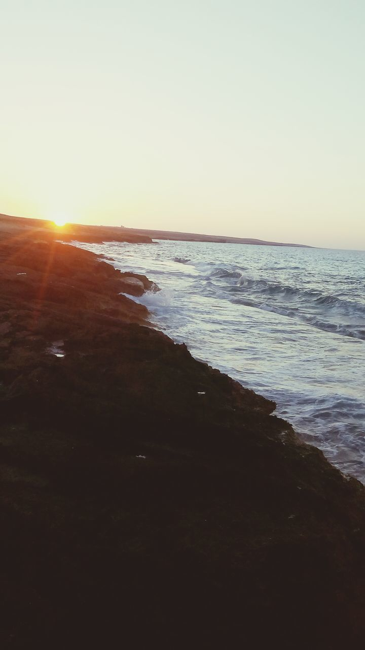 sea, scenics, beauty in nature, nature, sunset, horizon over water, tranquil scene, sun, beach, tranquility, sunlight, water, lens flare, copy space, sky, clear sky, no people, sand, outdoors, wave, day