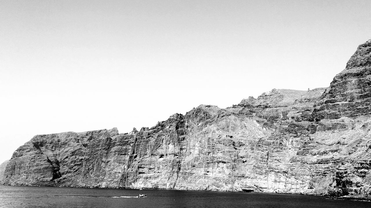 rock formation, rock - object, nature, clear sky, sea, copy space, water, beauty in nature, tranquility, cliff, scenics, mountain, physical geography, no people, day, tranquil scene, outdoors, waterfront, sky