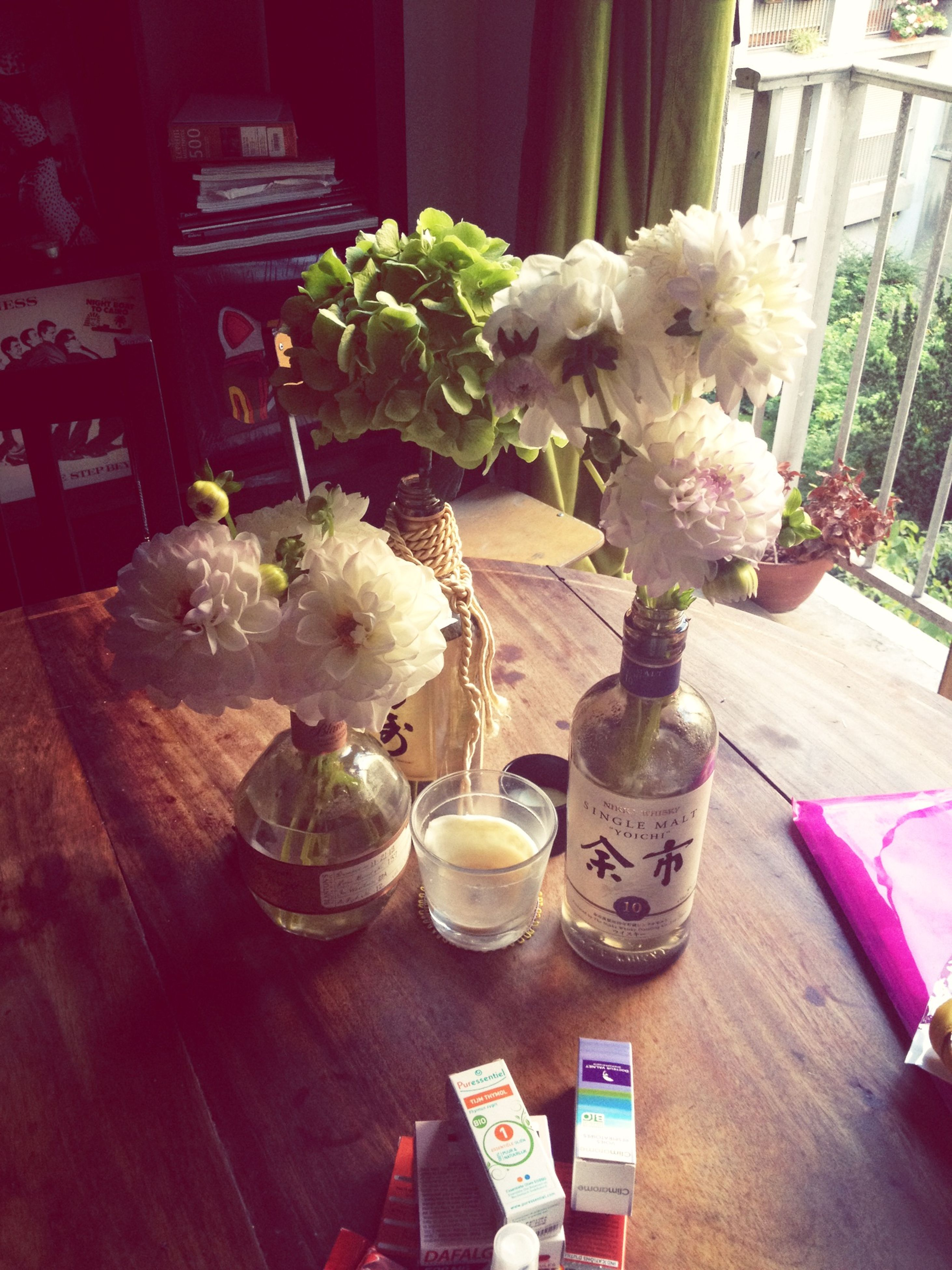 indoors, table, freshness, flower, vase, still life, food and drink, wood - material, glass - material, restaurant, drinking glass, home interior, drink, close-up, potted plant, variation, chair, no people, pink color, arrangement
