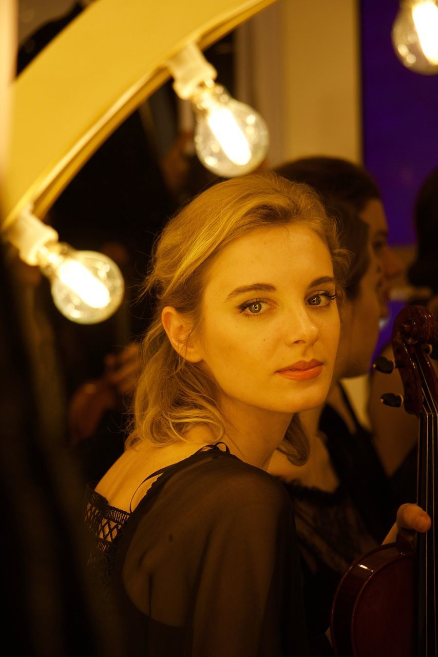 music, musician, real people, illuminated, looking at camera, portrait, one person, young adult, arts culture and entertainment, young women, indoors, night, headshot, musical instrument, performance, women, close-up, classical music, people