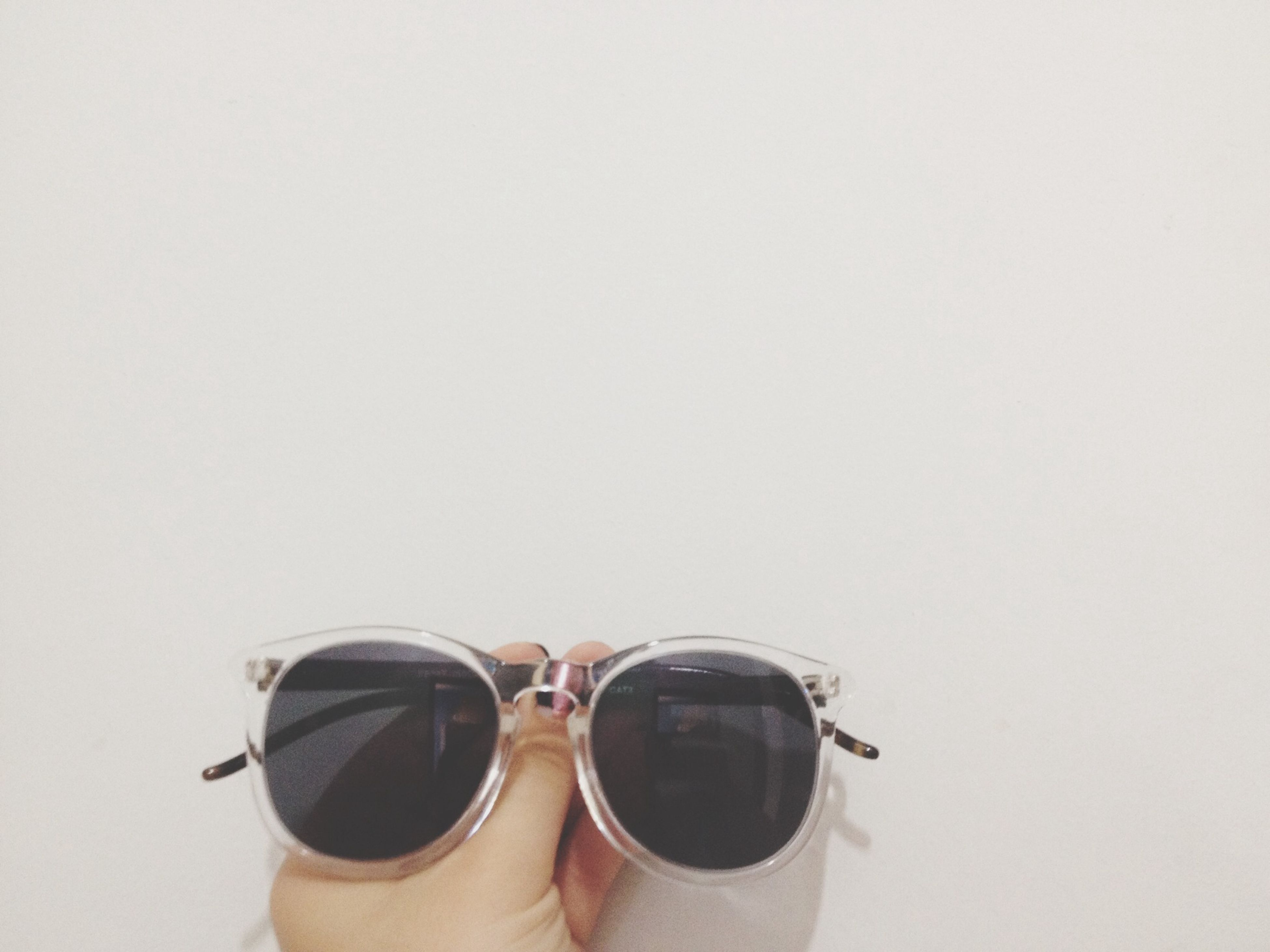 copy space, white background, studio shot, person, part of, lifestyles, personal perspective, holding, close-up, leisure activity, photography themes, unrecognizable person, cropped, clear sky, sunglasses, men, technology