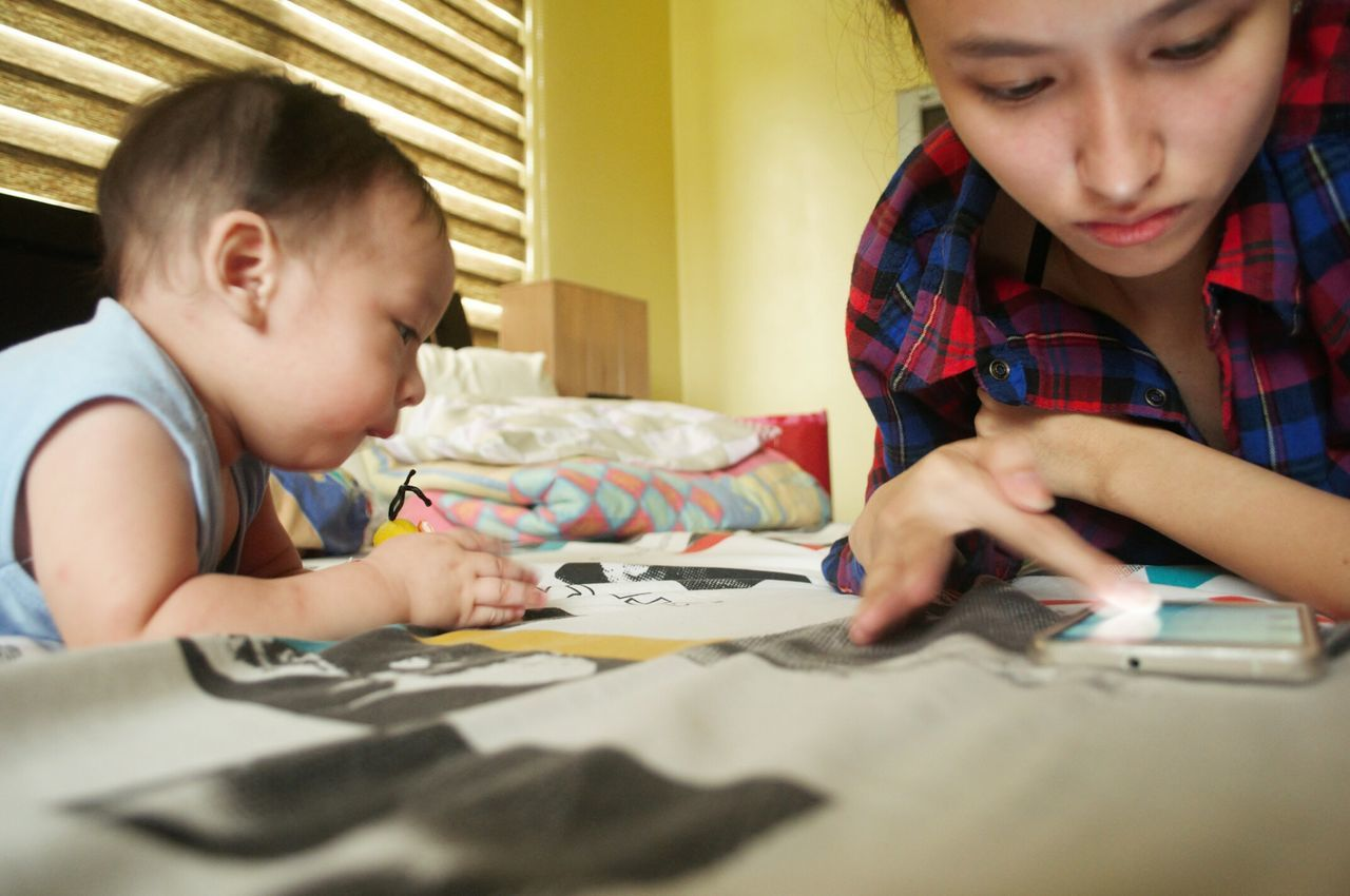 childhood, boys, indoors, home interior, child, real people, two people, playing, elementary age, paper, sibling, girls, bed, bedroom, friendship, day, human hand, close-up, people