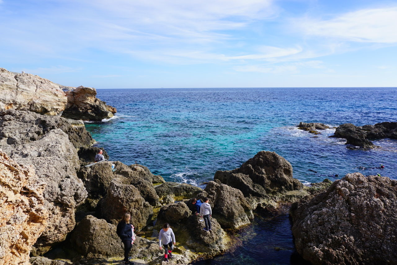 sea, horizon over water, sky, rock - object, nature, water, scenics, real people, beauty in nature, cloud - sky, day, outdoors, blue, tranquil scene, tranquility, leisure activity, beach, men, one person, people