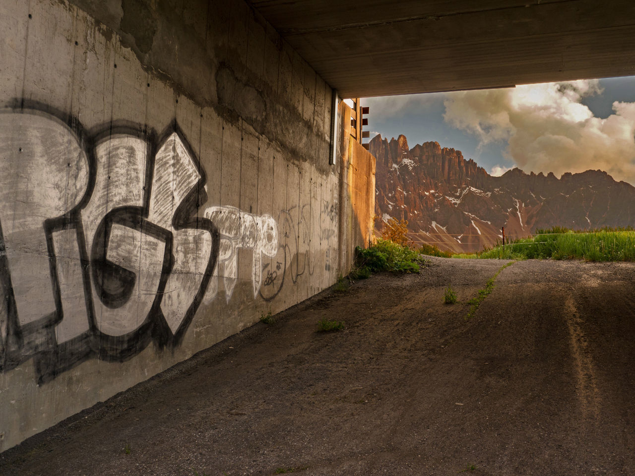 a graffity in opposite to the great dolomite panorama Alpen Alpes Bridge - Man Made Structure Built Structure Clouds And Sky Day Different Is Better . ❤ Different Points Of View Dolomites Dolomites, Italy Graffiti Mountains No People Nova Levante Outdoors Social Issues Spray Paint Streetphotography Summer Evening Summer Views Südtirol Welschnofen