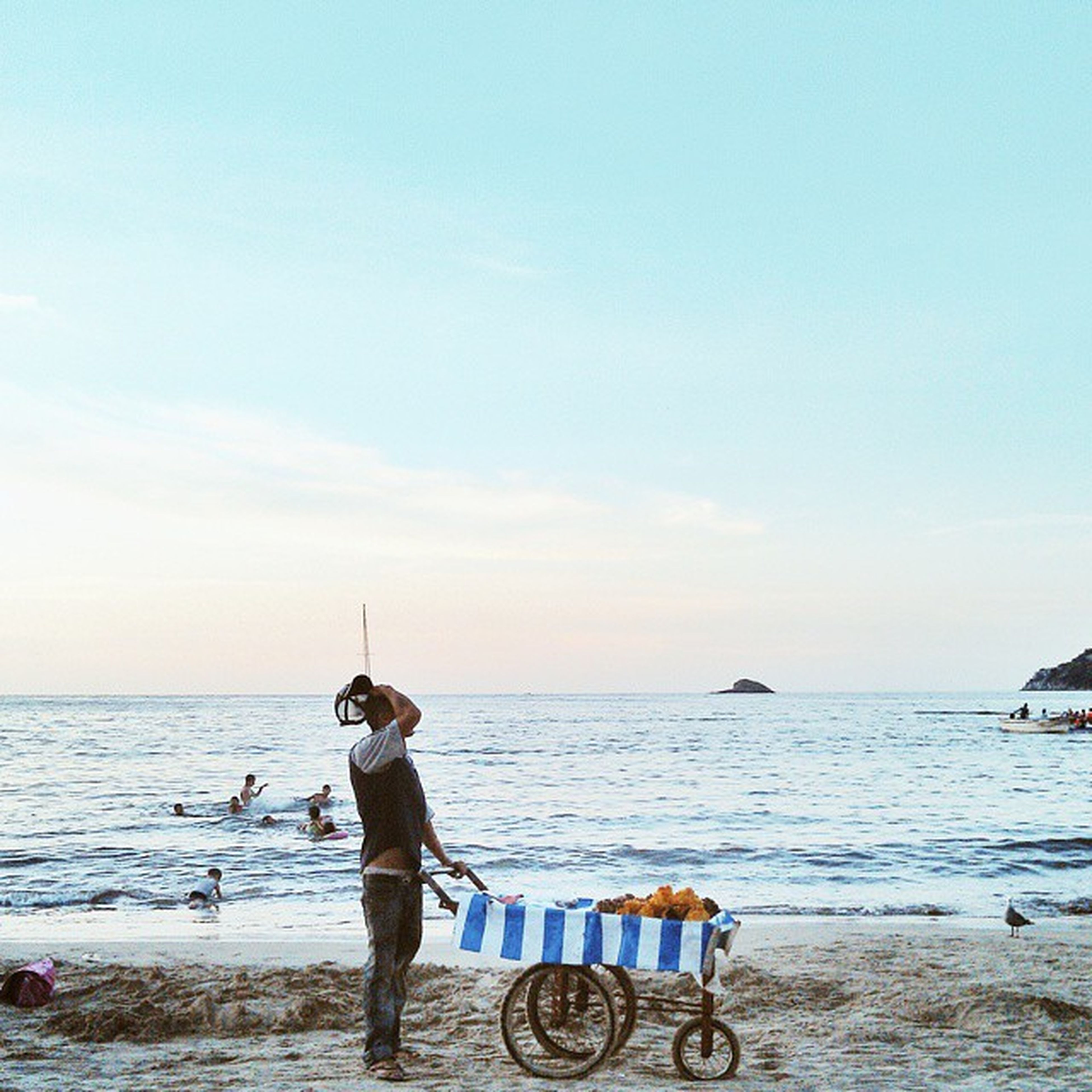 sea, horizon over water, water, beach, lifestyles, leisure activity, shore, sky, full length, men, transportation, nature, vacations, mode of transport, beauty in nature, rear view, tranquility