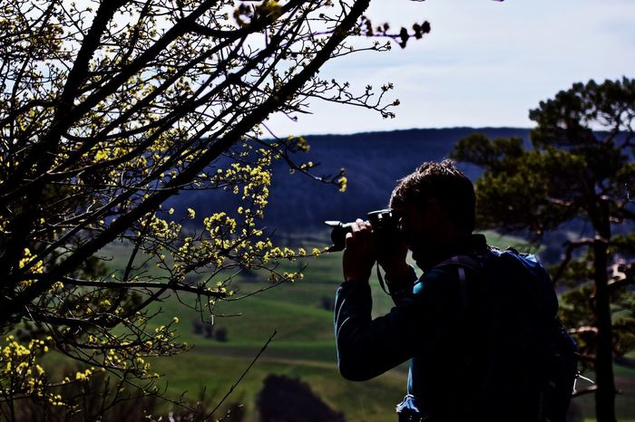 Photography Themes Tree Photographing Real People Camera - Photographic Equipment Leisure Activity Men One Person Outdoors Photographer Growth Lifestyles Nature Wireless Technology Mobile Phone Standing Silhouette Branch Day