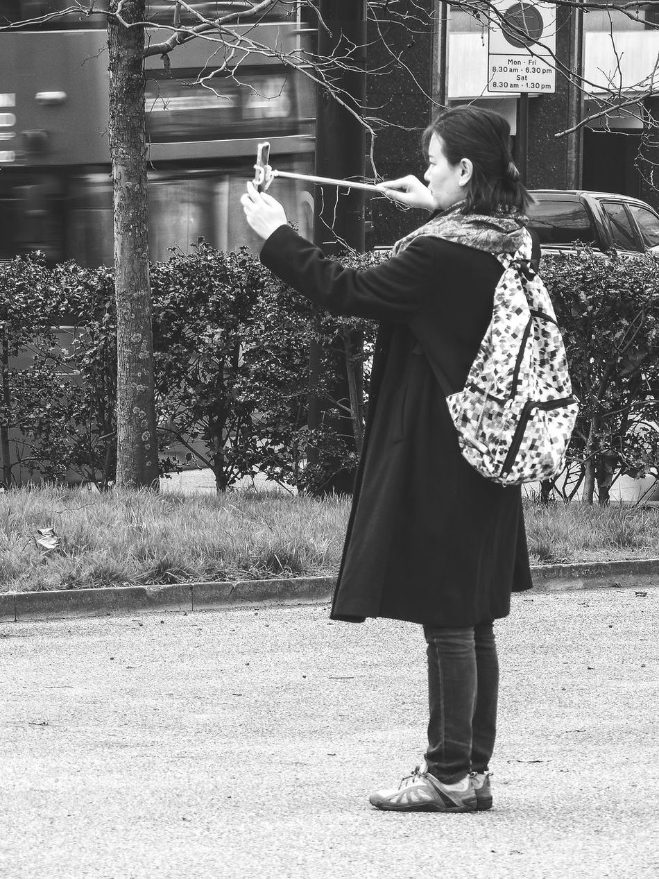 Taking A Selfie One Person Adults Only Full Length Adult Outdoors People Young Adult Black And White Monochrome Visit London Hyde Park, London Tourist Street Photography People Watching Day Posing Selfie Stick Selfie Coat Overcoat Bag Knapsack