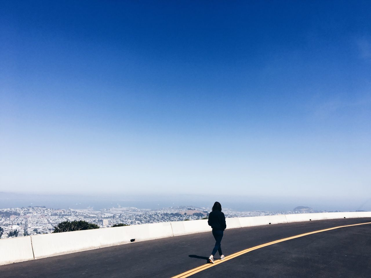 copy space, clear sky, blue, nature, real people, road, one person, full length, outdoors, day, transportation, leisure activity, winter, sunlight, scenics, snow, lifestyles, landscape, women, beauty in nature, mountain, cold temperature, sky, people