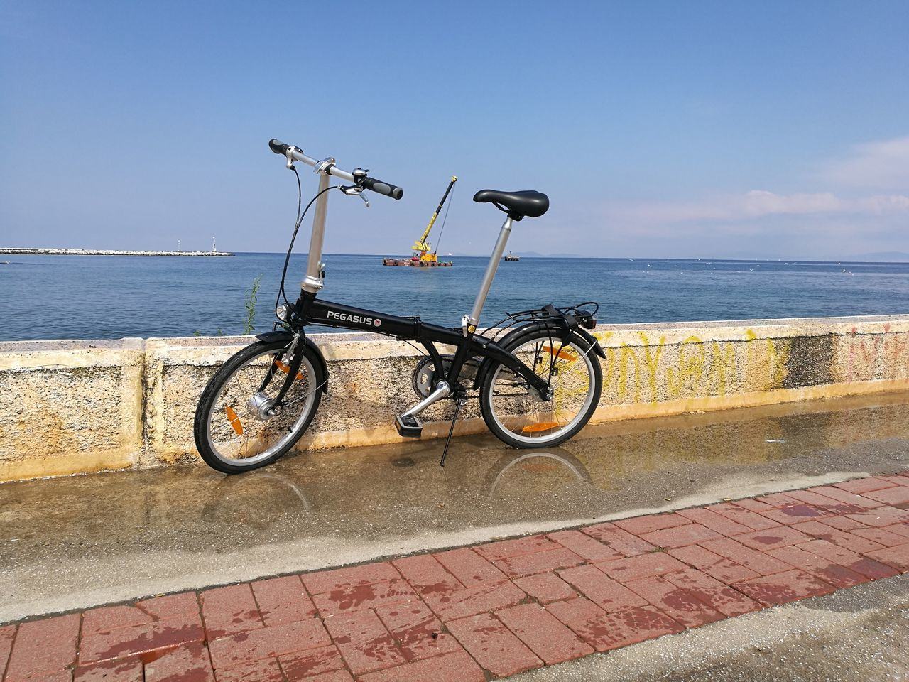 bicycle, transportation, sea, stationary, water, day, outdoors, no people, mode of transport, horizon over water, sky, nature, land vehicle, retaining wall, clear sky, beauty in nature
