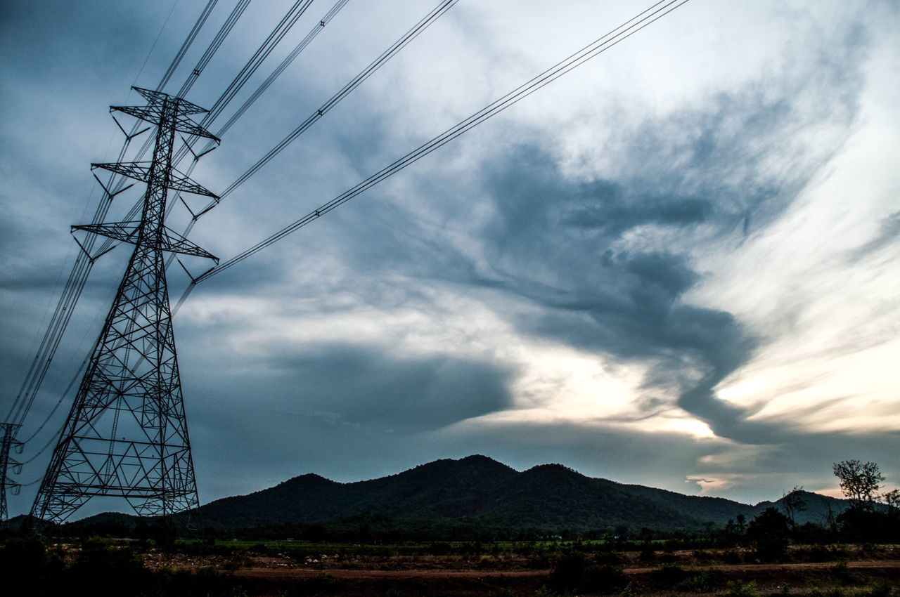 Electricity Pylon On Field By Mountain Against Sky At Dusk